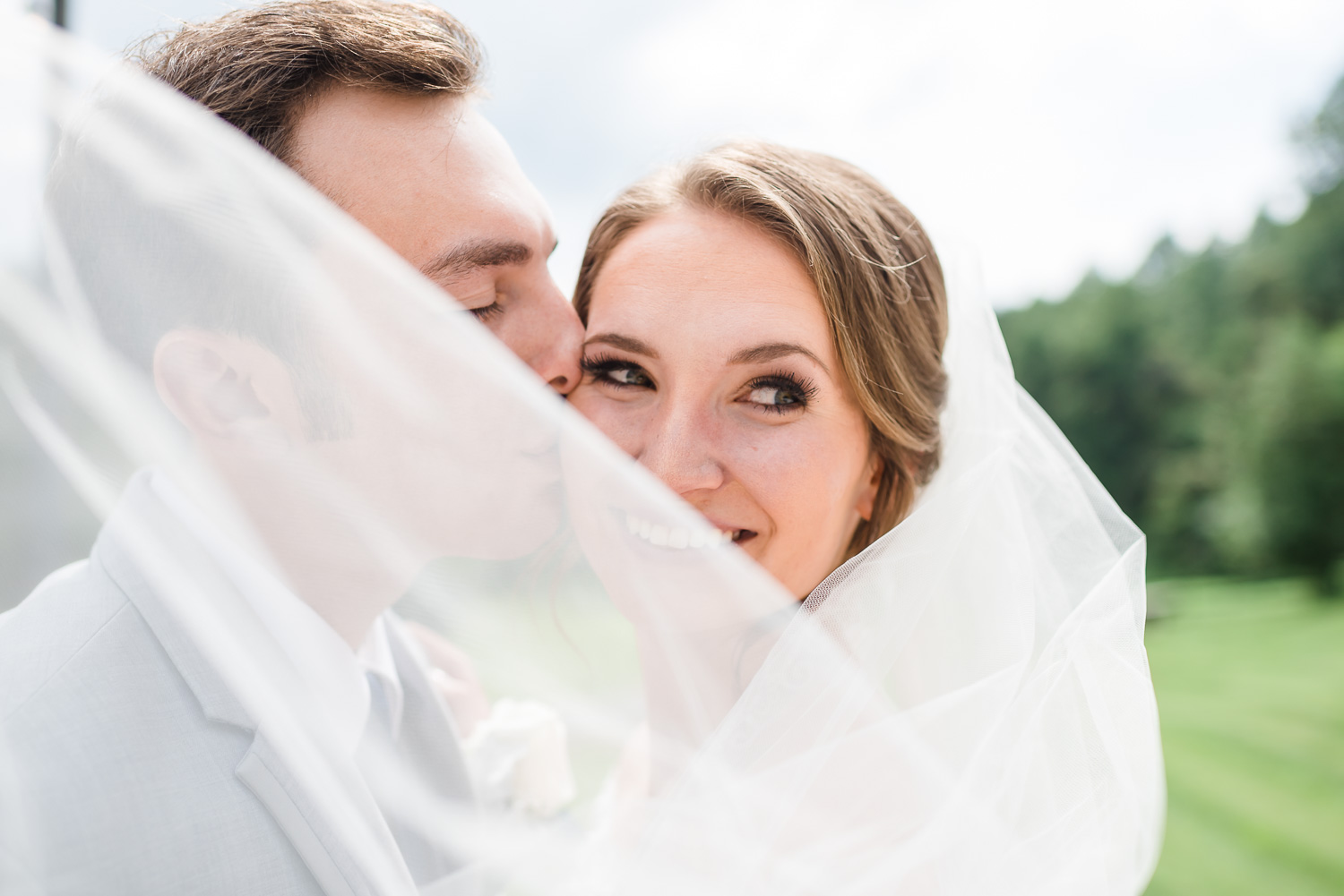 bride and groom outside with wind blowing through white veil
