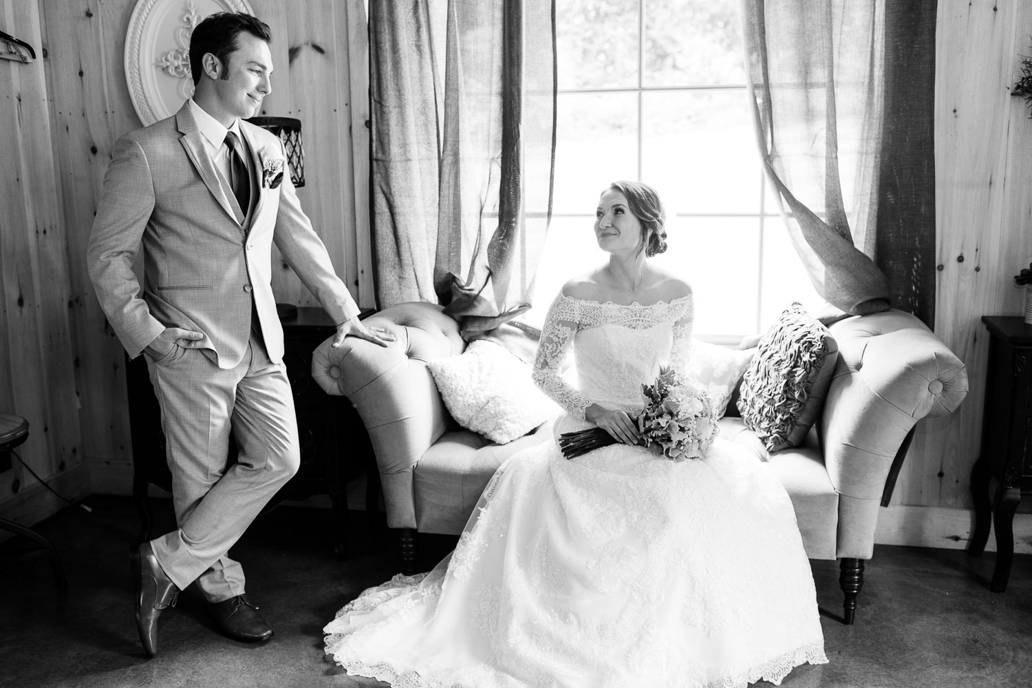 black and white photo of a groom looking at his bride sitting on a vintage couch in the bride room at The 4 Points Farm in Sevierville TN