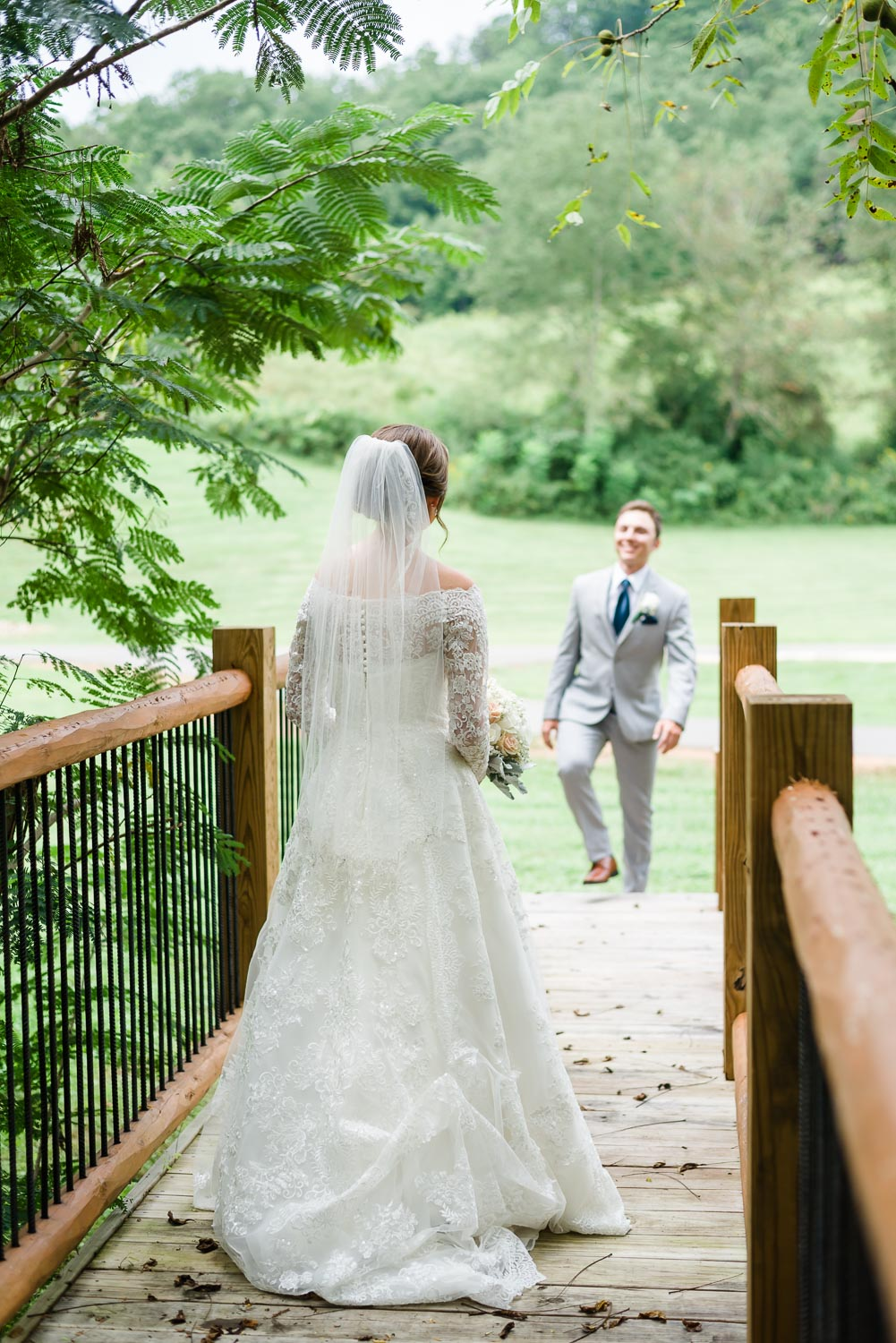 groom walking towards his bride outside on the bridge at 4 points Farm in Gatlinburg TN