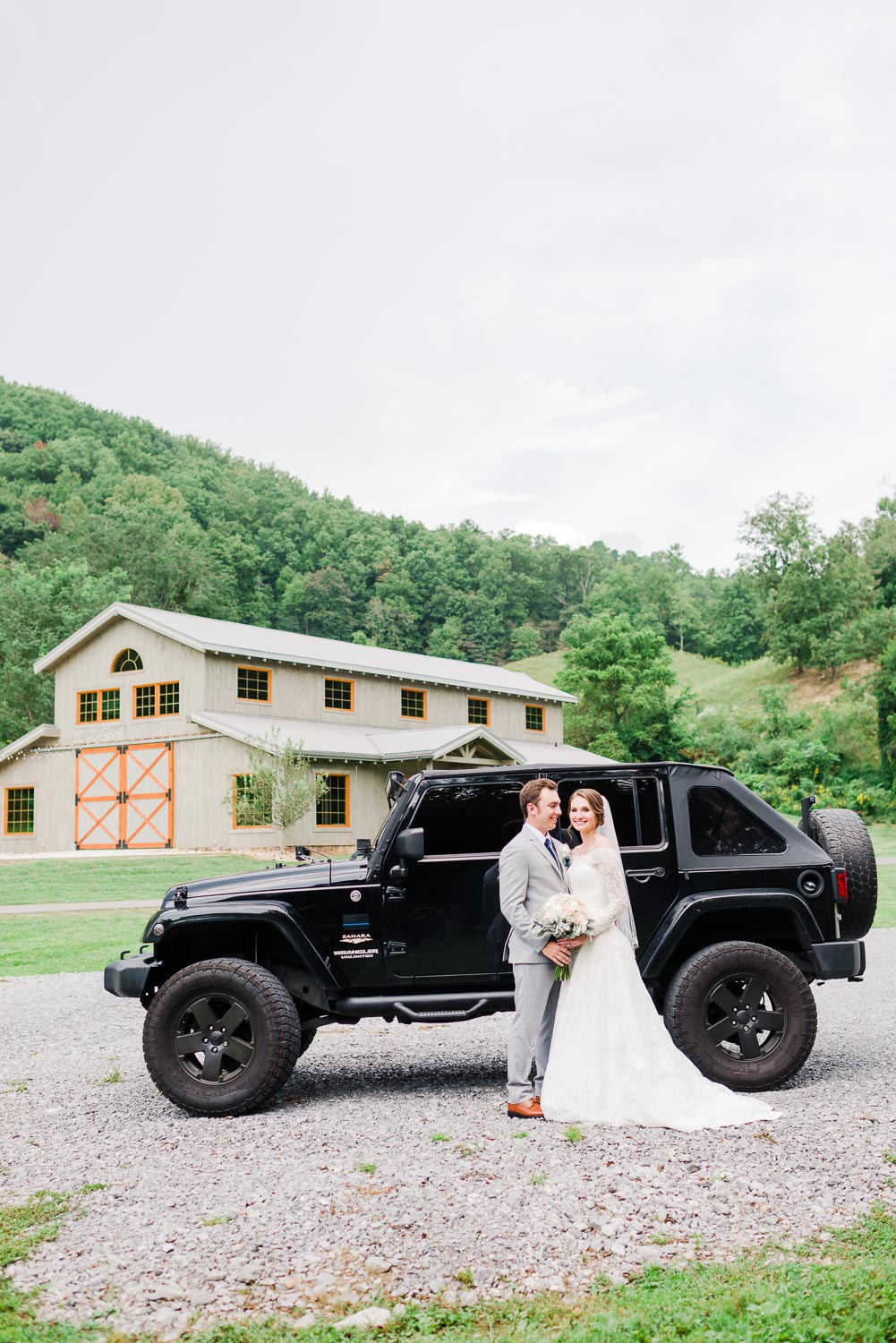 bride and groom in front of a black jeep with the barn at 4 Points Farm in the background