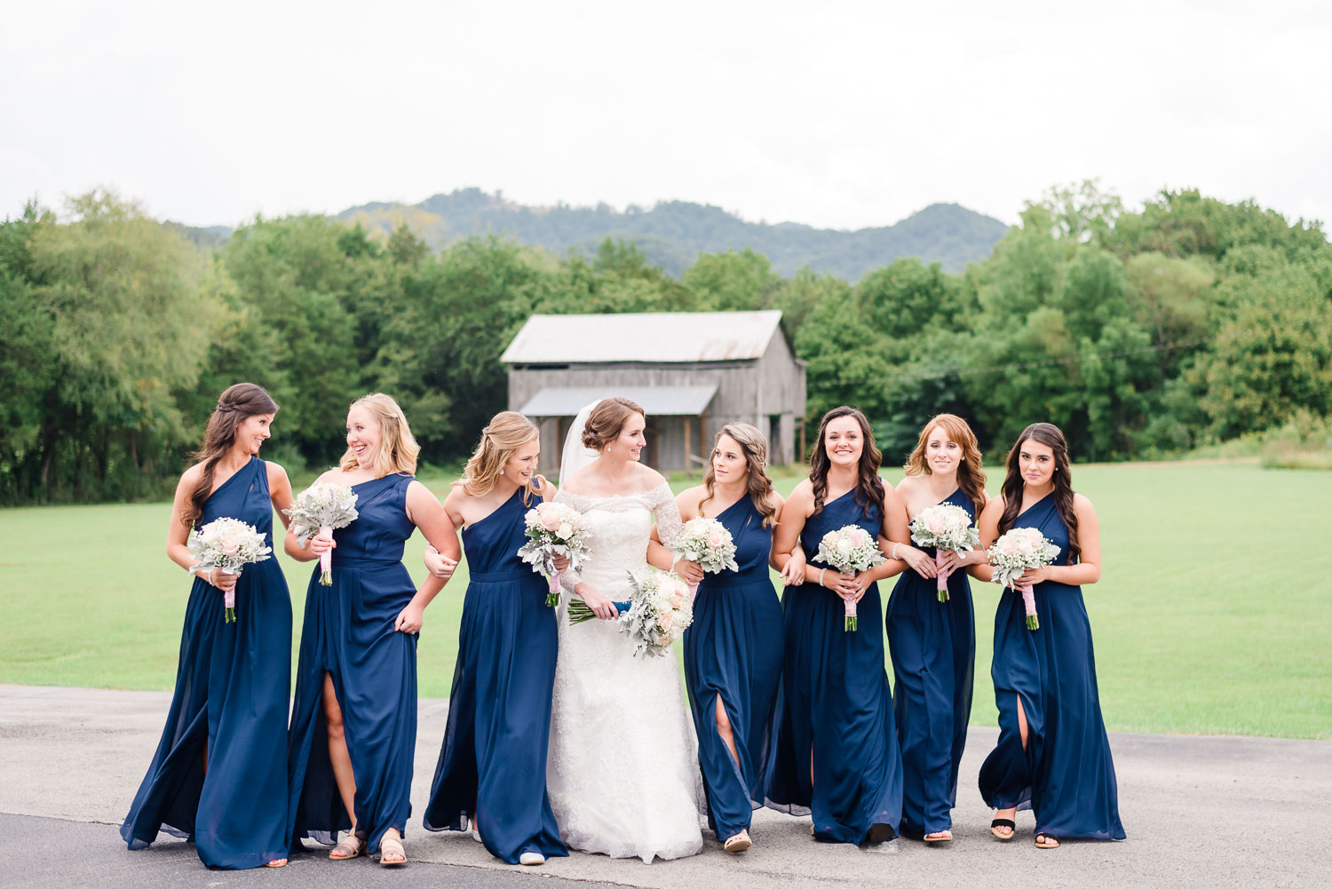 bridesmaids in navy and bride in white Oled Cassini wedding dress in front of a rustic barn in Gatlinburg TN