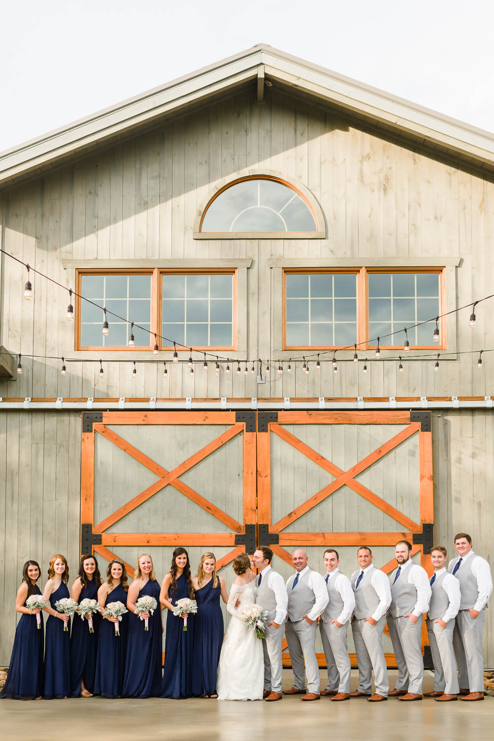 wedding party right in front of the big wooden doors of the barn at 4Points Farm venue in Gatlinburg TN