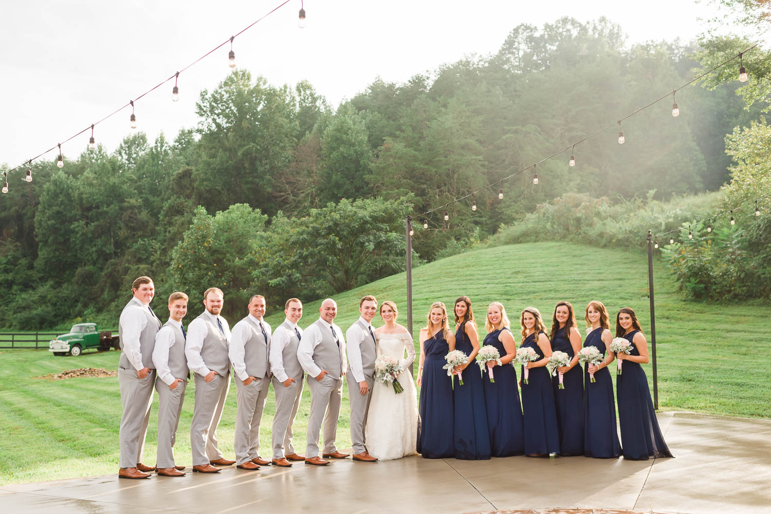 wedding party with guys in gray vests and girls in navy bridesmaids dresses outside at sunset in Gatlinburg TN