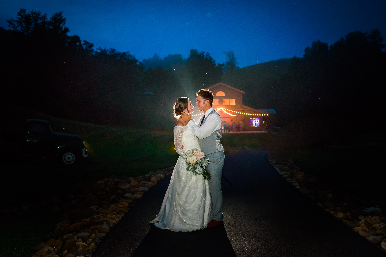 bride and groom at night with rim lighting and the venue at 4 points Farm softly in the background.