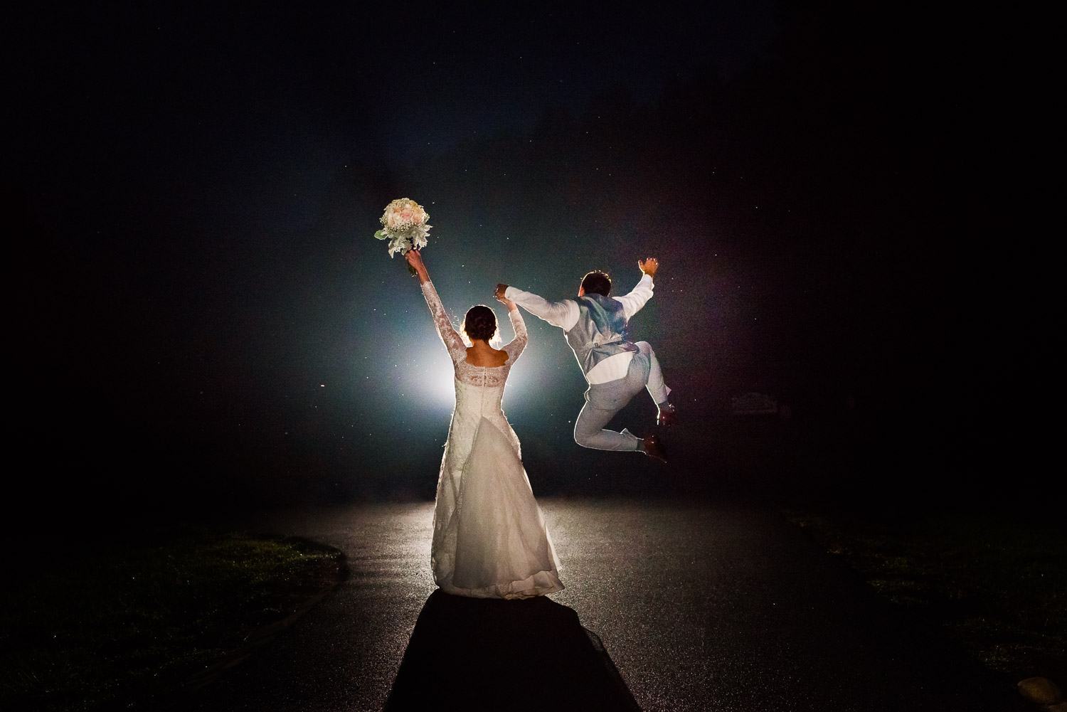 bride with flowers raised in her left hand holding her groom's hand as he jumps high and clicks his heels together happily heading off into their future at night.