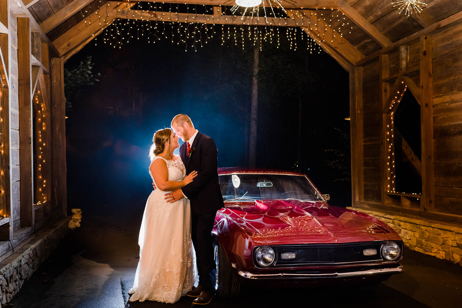 Bride and groom at night in front of a red 1968 Camaro in a covered bridge in North Georgia