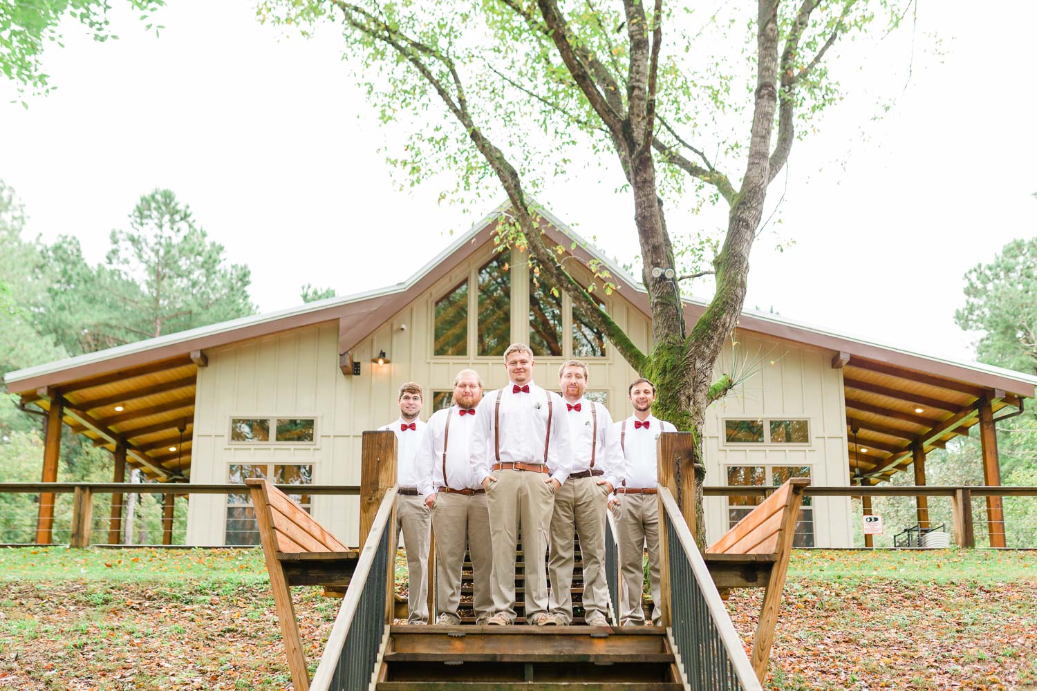 Groomsmen in tan pants and red bowties with suspenders outside by the Hiwassee River in TN