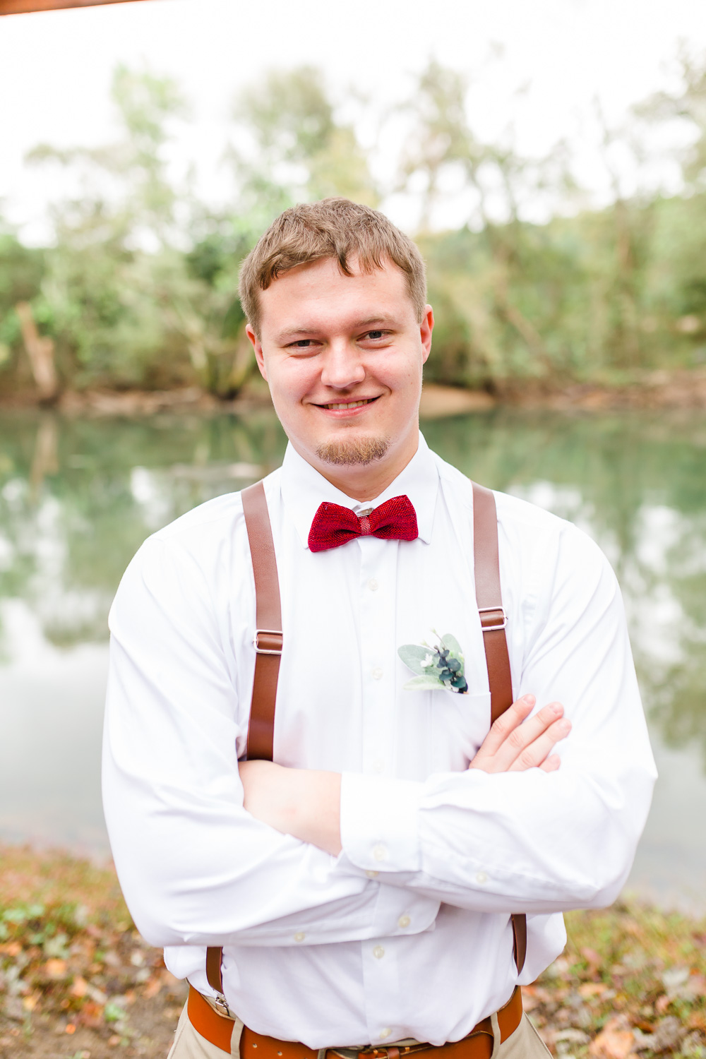 one guy outside in white shirt, red bowtie, and leather suspenders with the river in the background