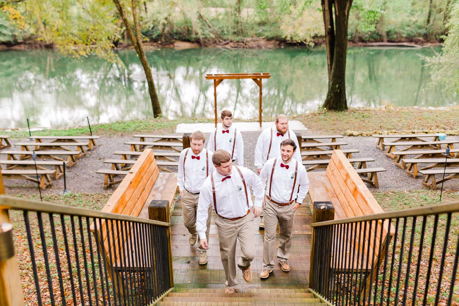 Groomsmen walking up the stairs with the riverside ceremony site in the background at Hiwassee River weddings in Delano TN