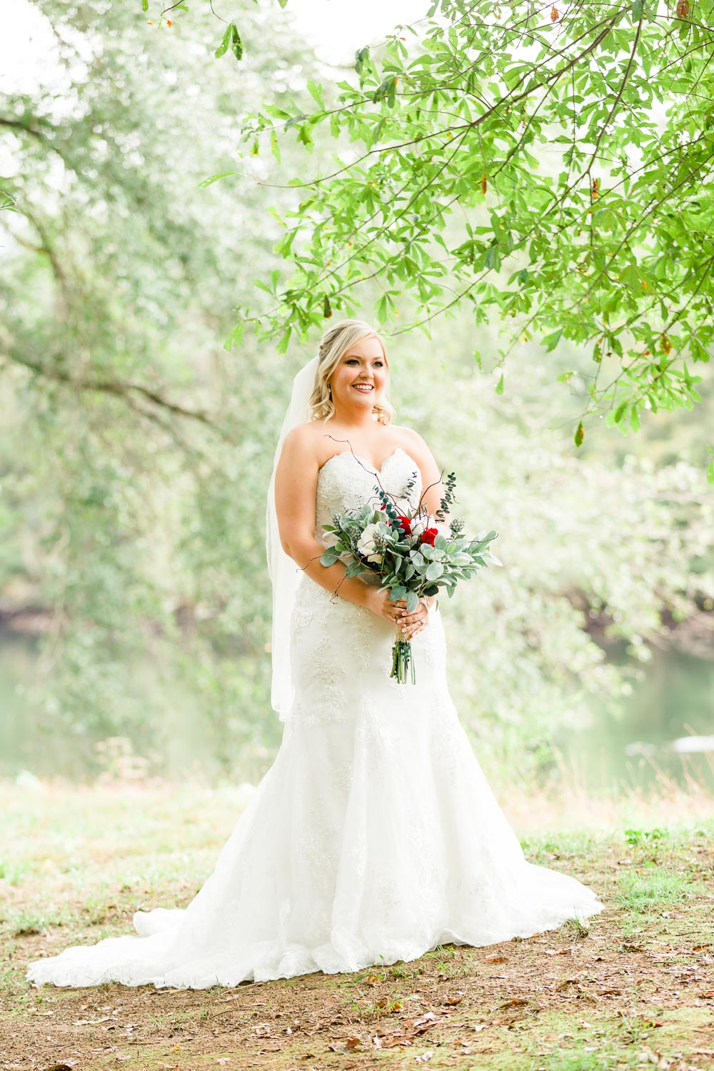 bride outside onder green trees by the river in October