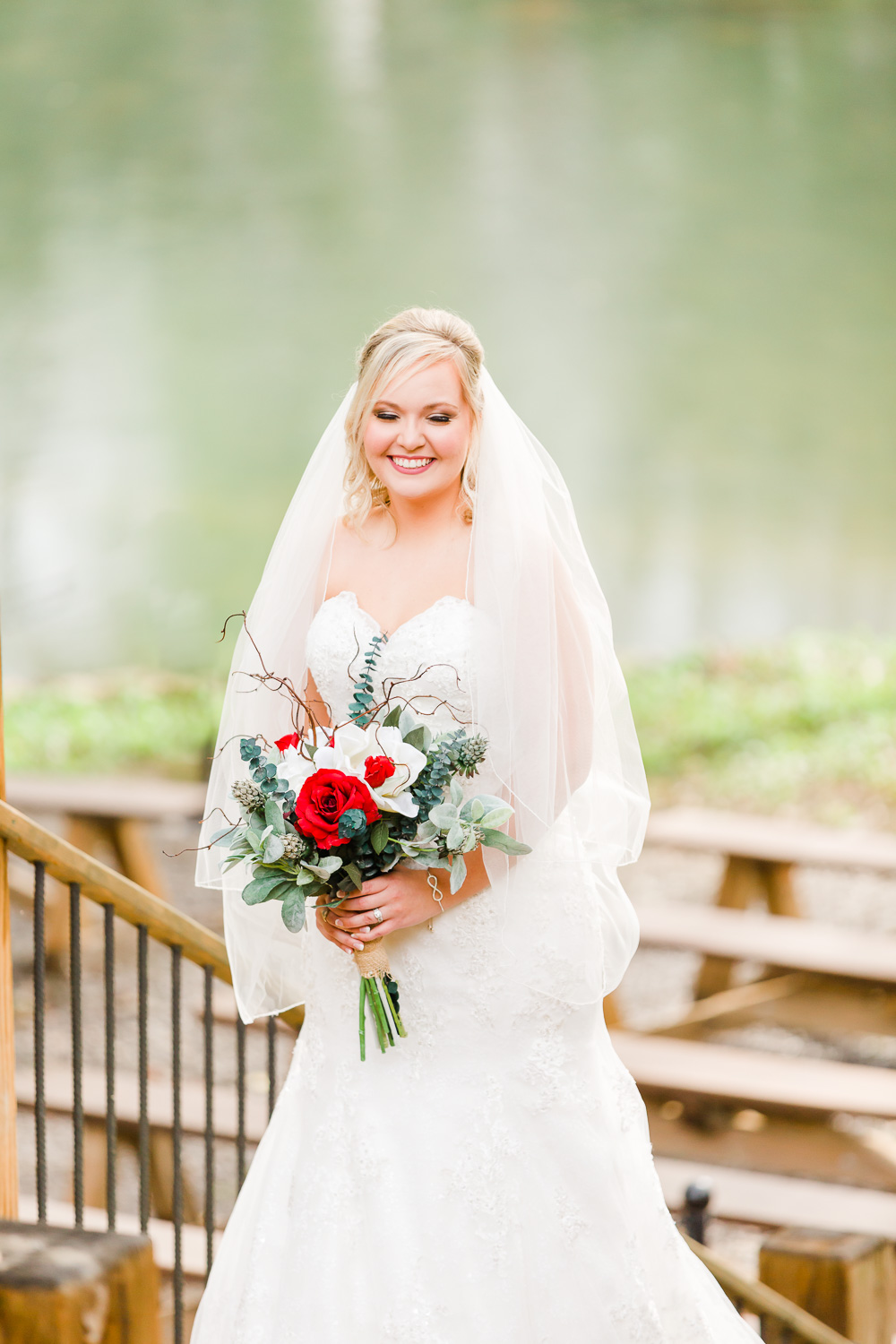 a bride holding red and white fall flowers with just the river in the background