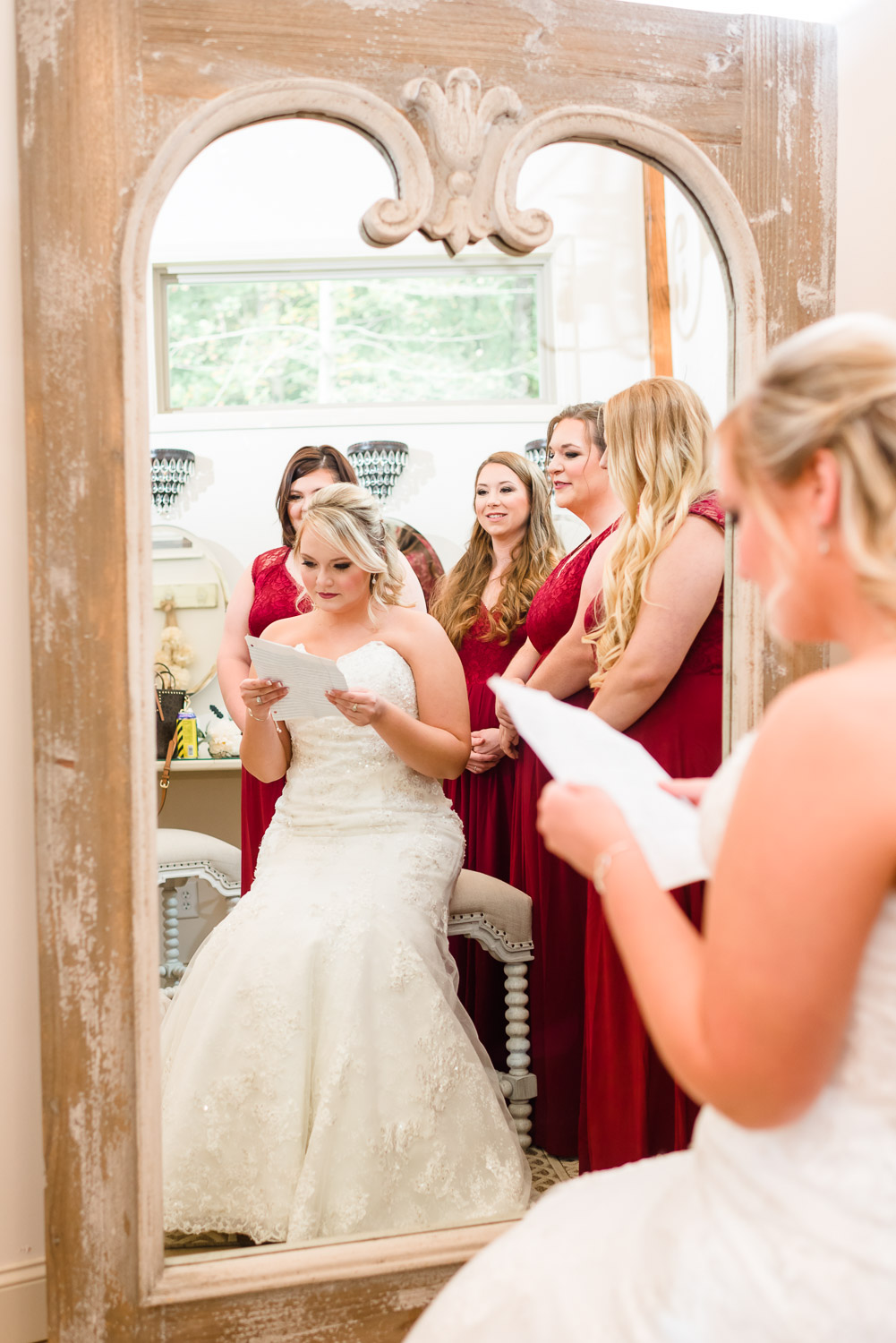 reflection in mirror of bride reading a letter from groom with her bridesmaids wearing red in the background