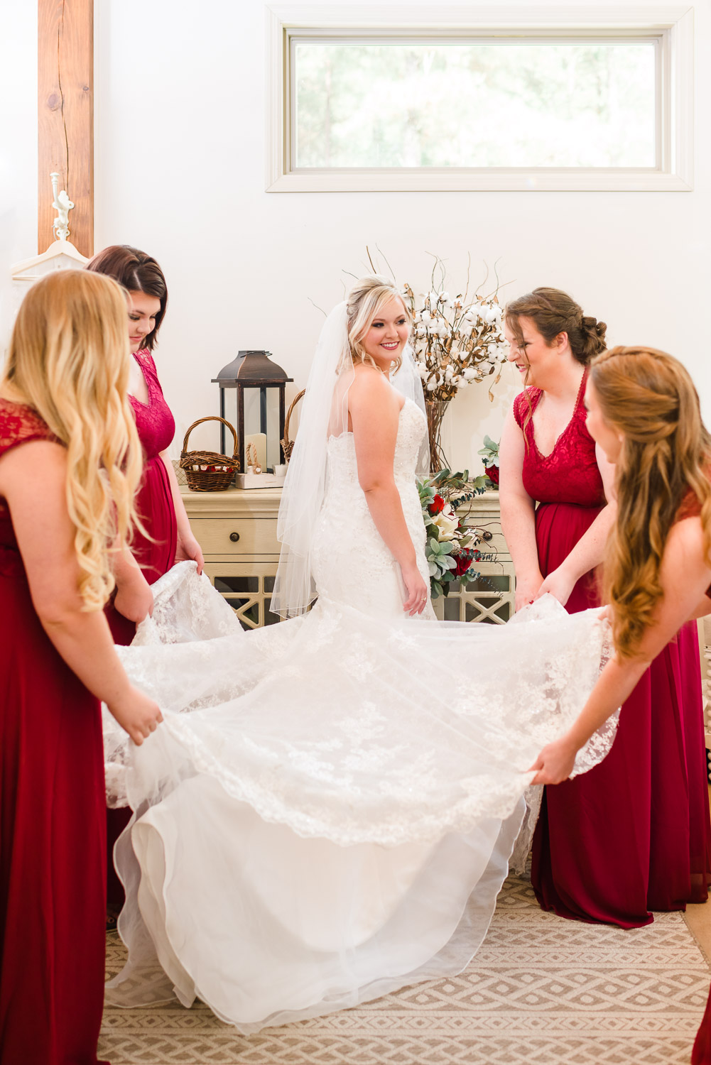 Bridesmaids wearing cranberry red dresses helping bride lay her train out on her wedding day.