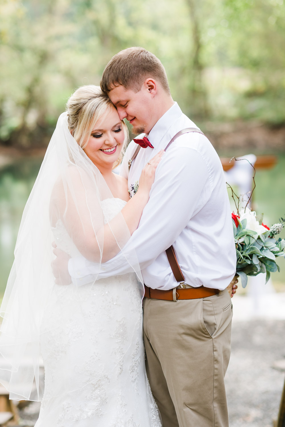 smiling bride in her groom's arms outside with red, white and greenery bouquet