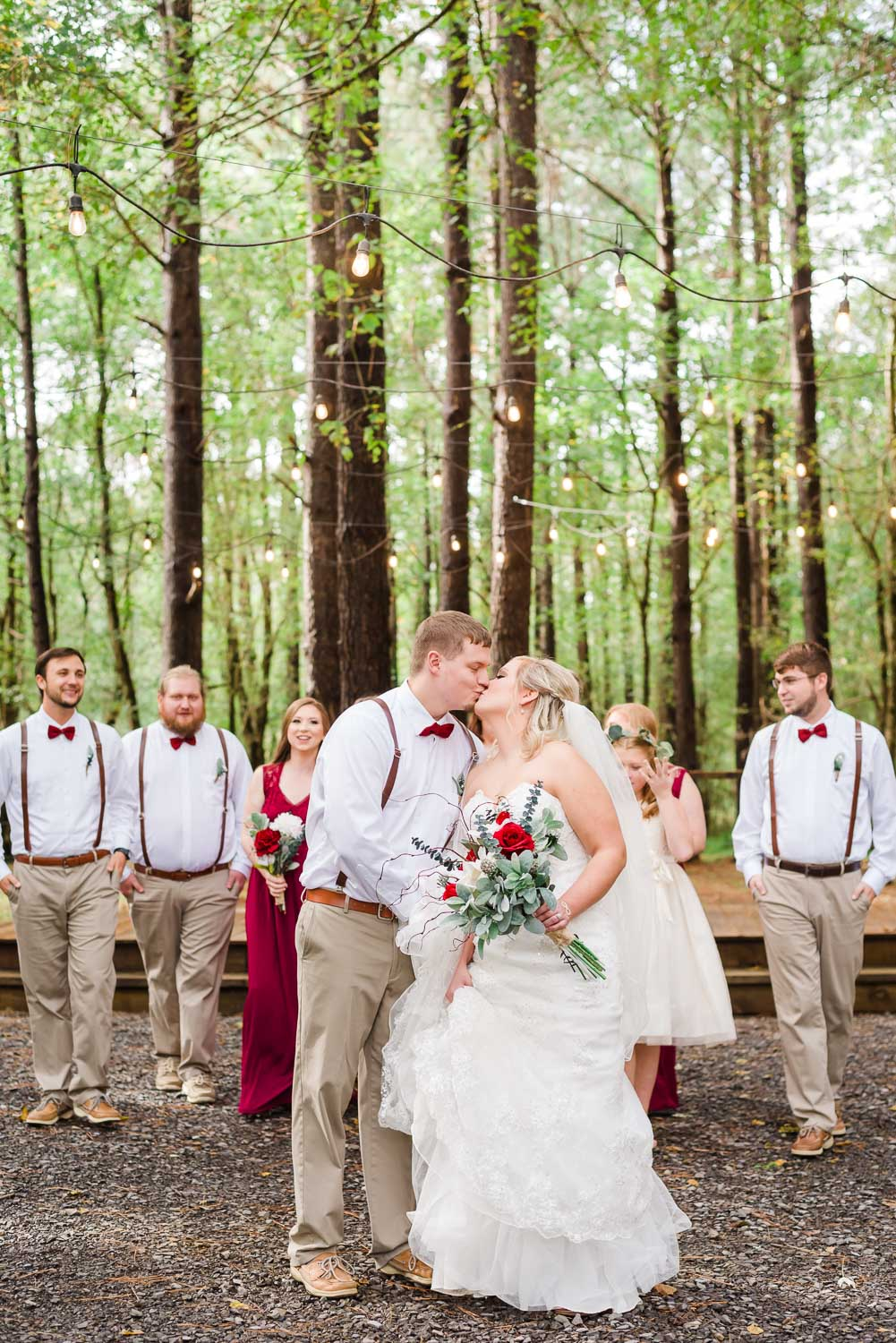 bride and groom and wedding party walking laughing and talking under the twinkly lights of the Forest Ceremony site at Hiwassee River weddings in October.