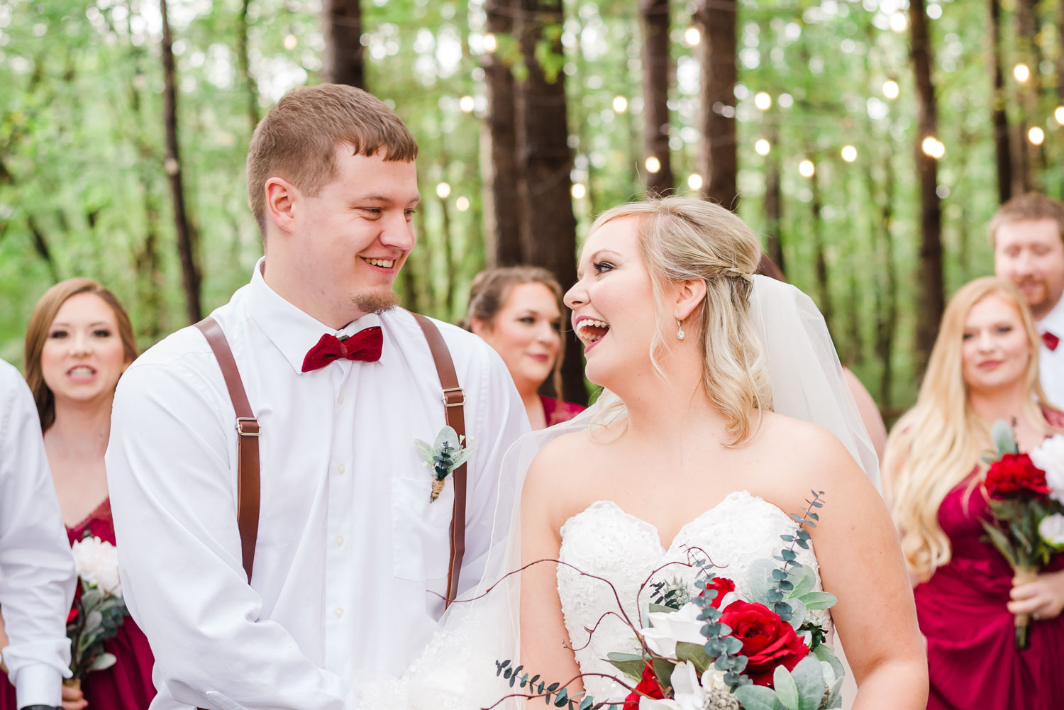 bride and groom outside under twinkly lights in the woods