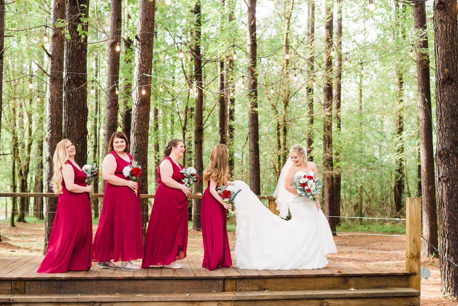 bridesmaids helping bride walk across stage at the Forest Ceremony site in the tall Pines
