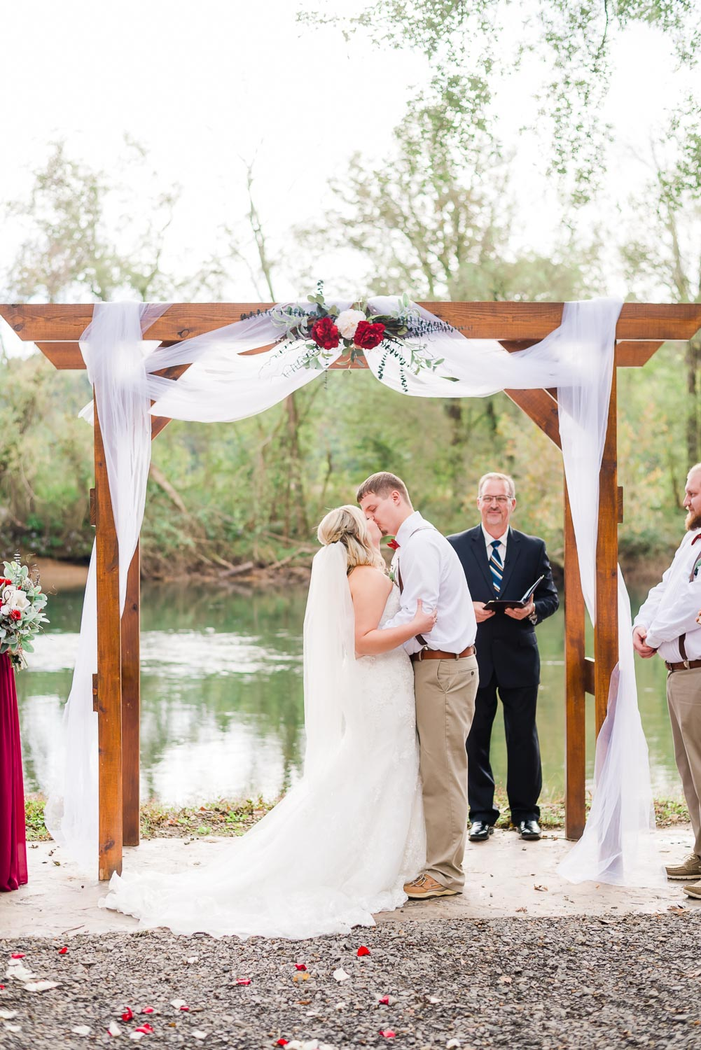 Bride and groom's first kiss as a married couple at their outdoor riverside wedding in TN
