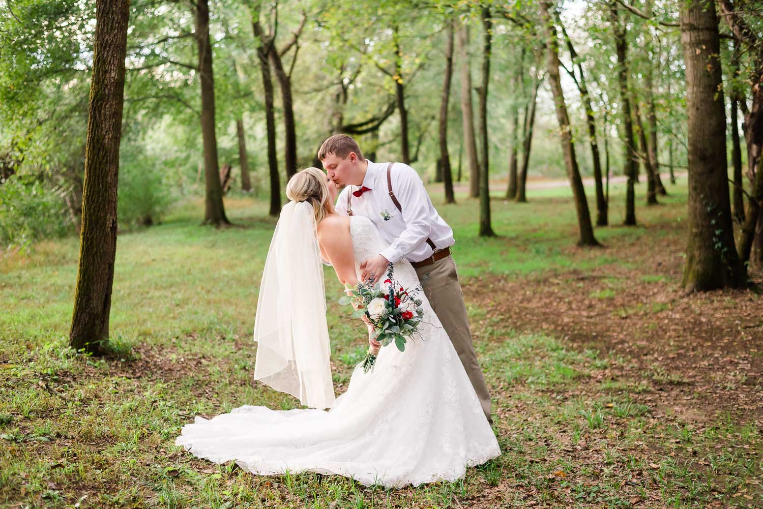 bride and groom stopping for a kiss in the woods as the sun sets in Tennessee