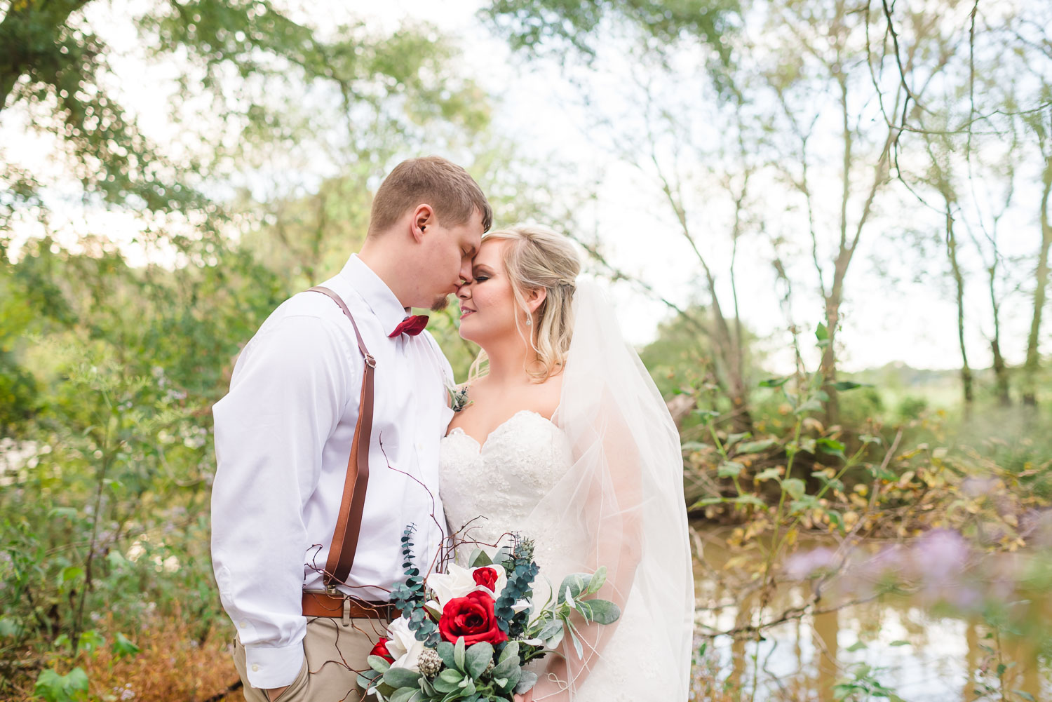 groom in white button down shirt and bowtie, and bride with red, bold red fall colored bouquet outside in lavendar Asters