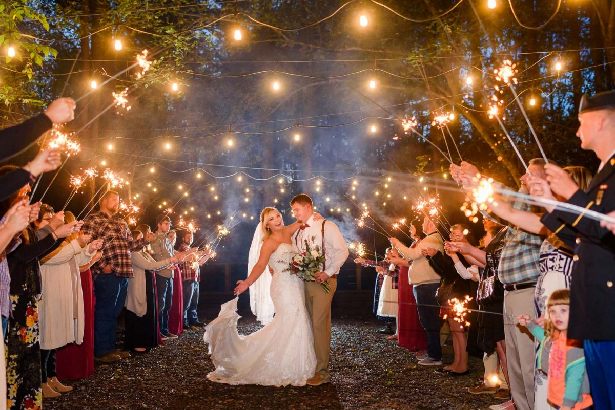 Nelya Photographer night time wedding sparkler exit under twinkly lights at Hiwassee River Weddings