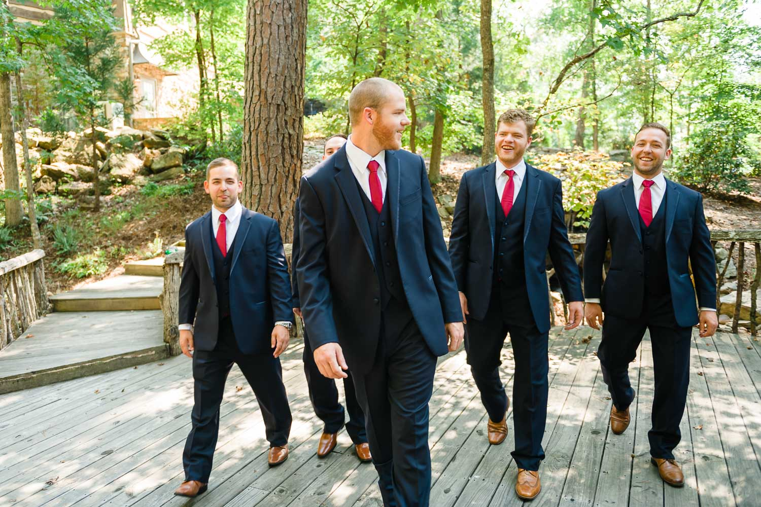groom and groomsmen in dark suits walking at Indigo Falls venue in GA