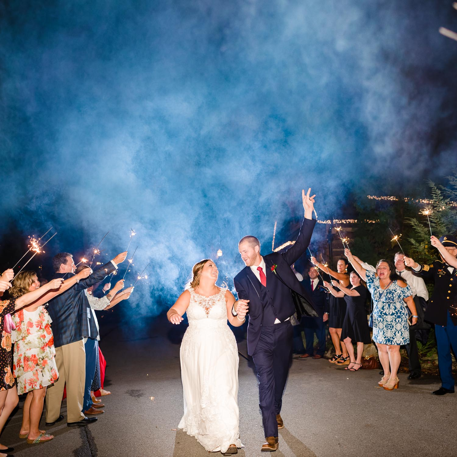 blue smoke from wedding sparklers and bride and groom danging under sparklers