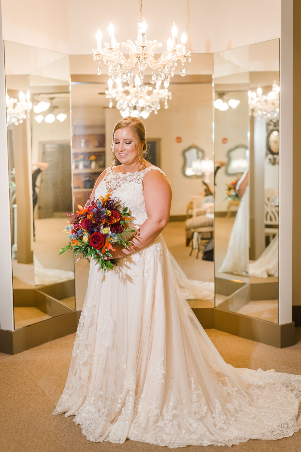 bride holding fall colored bouquet in front of mirrors at Indigo Falls in Dallas GA