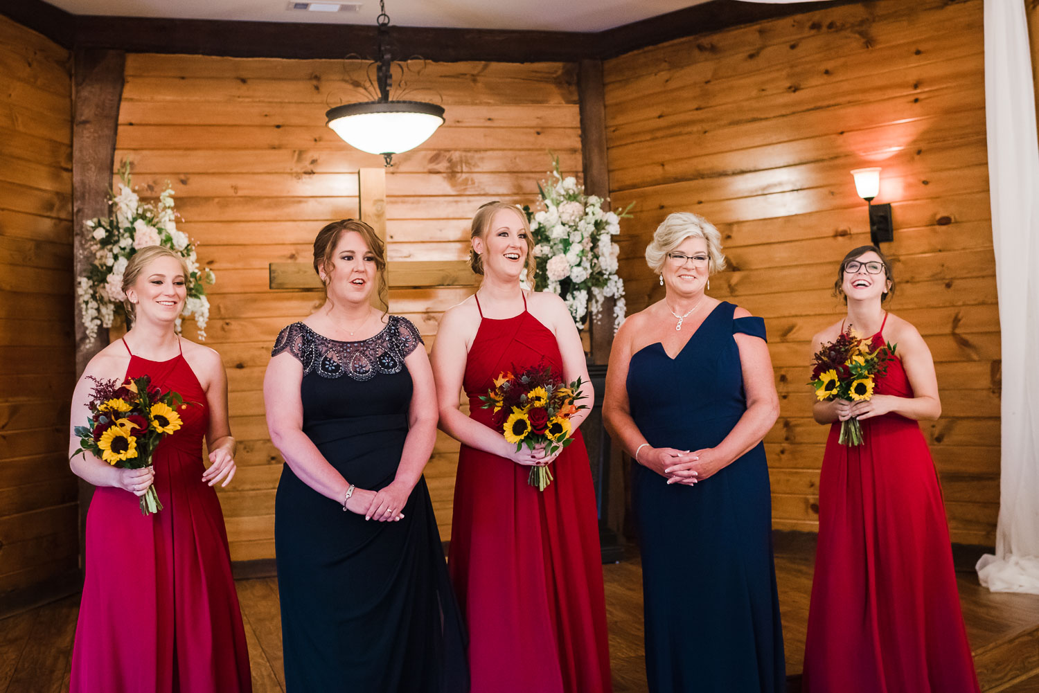 bridesmaids wearing deep red wine colored long dresses and moms wearing navy blue dresses