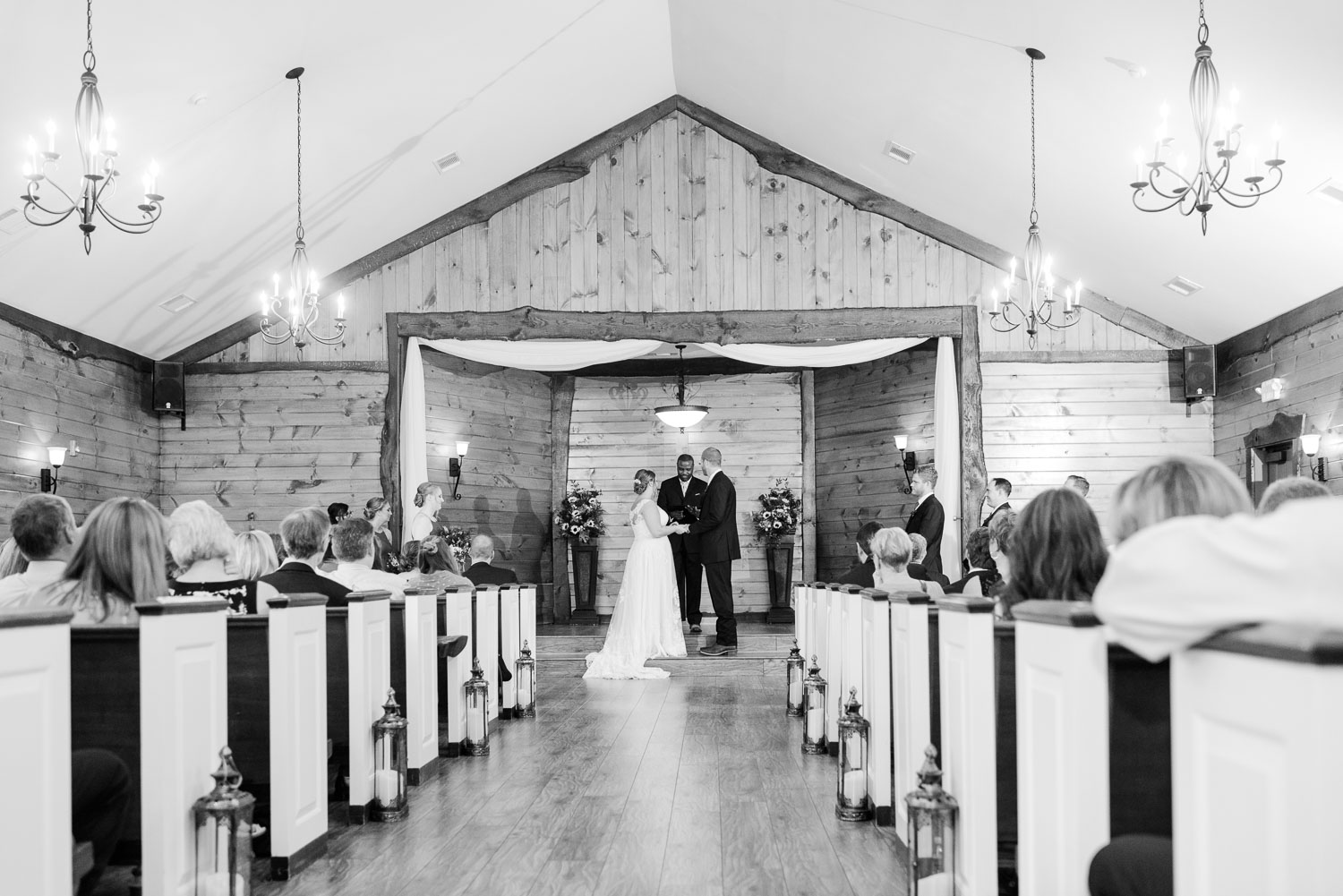 black and white wide angle view of indoor wedding ceremony in the chapel at Indigo falls