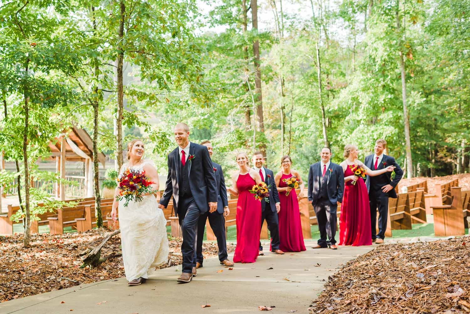 bride and groom plus bridal party walking along concrete path in October at Indigo Falls wedding venue in North West GA