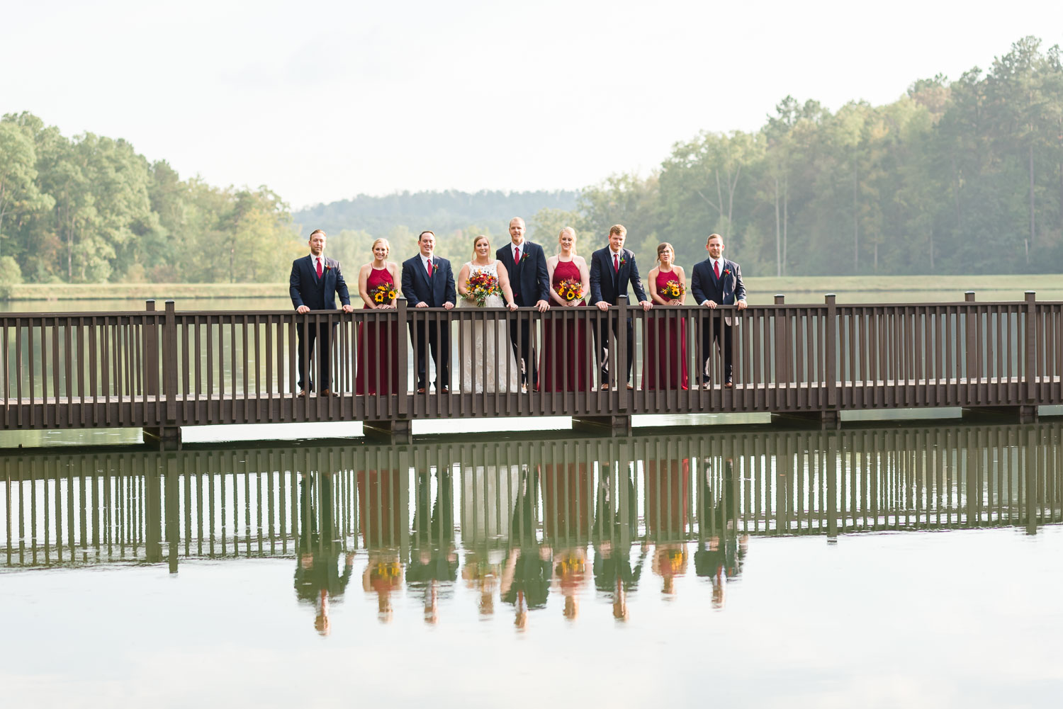 bridal party group on bridge across lower pond at Indigo falls venue in Dallas GA