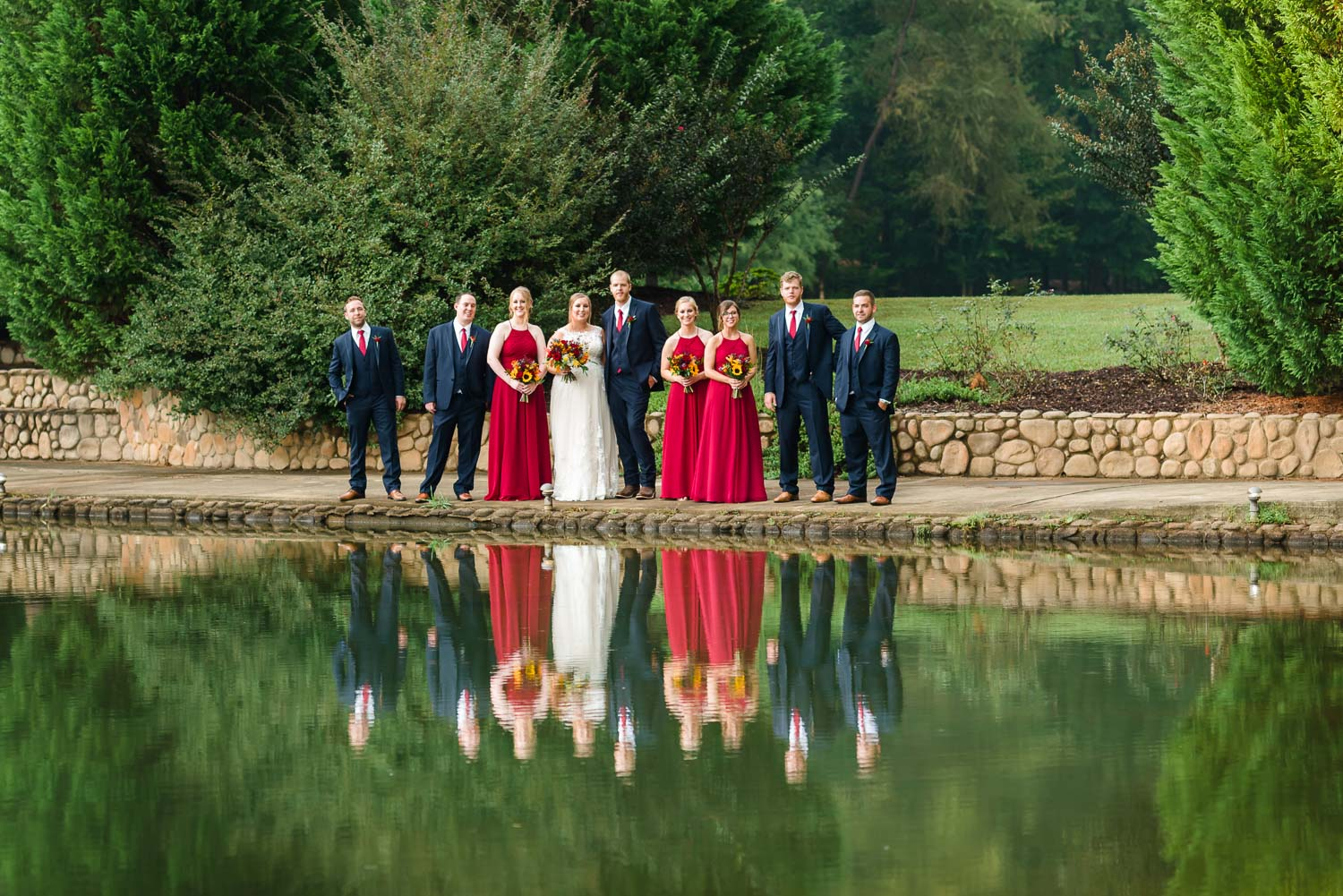 red white and blue wwedding party standing at edge of pond with fullreflections of them in the water