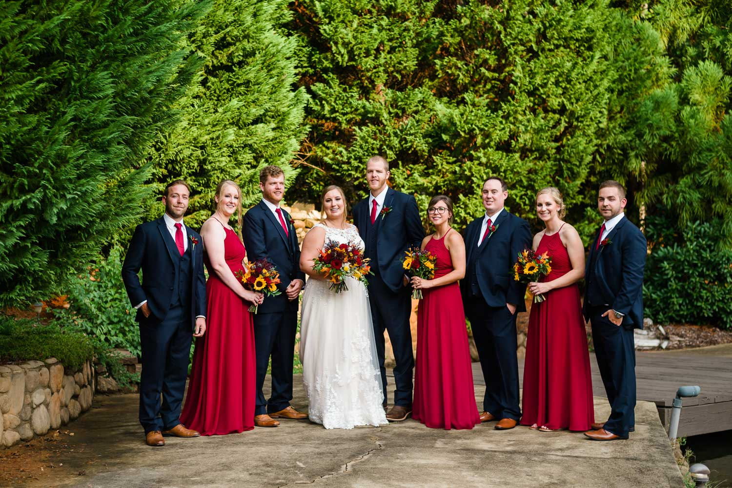 hockey goalie gets married at Indigo Falls with wedding party in deep red and navy.