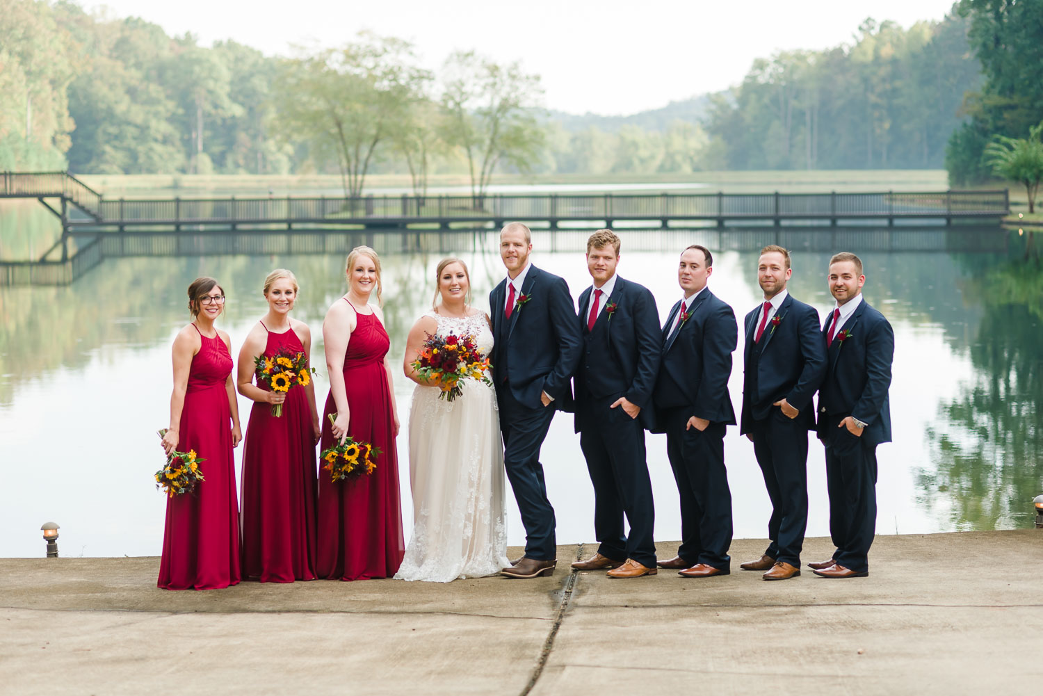 wedding party wearing navy suits and red dresses in front of lower pond at Indigo Falls venue in Dallas GA