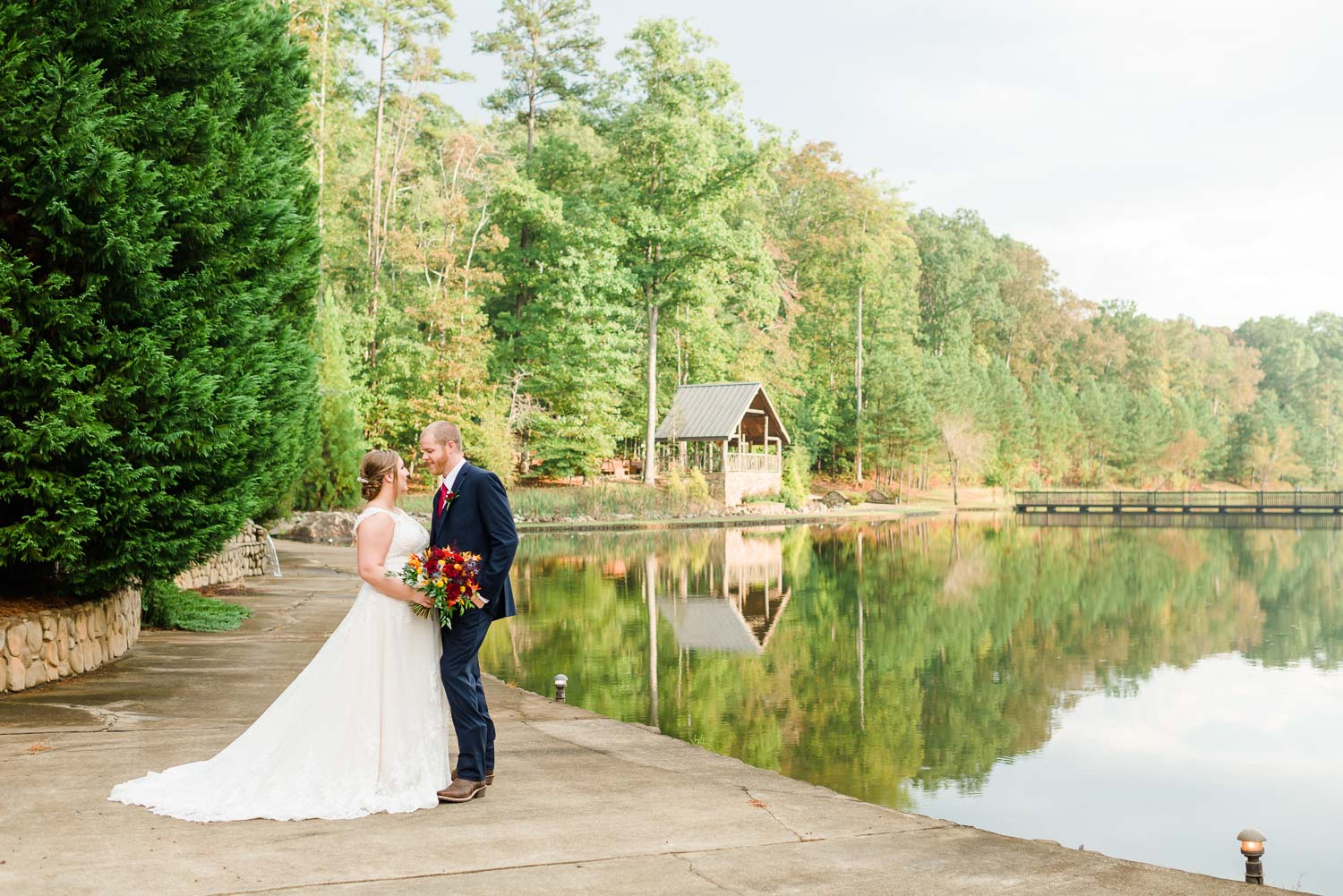 wide angle view of the pond with trees reflecting in the water and the bride and groom standing on the walkway at Indigo Falls in GA.