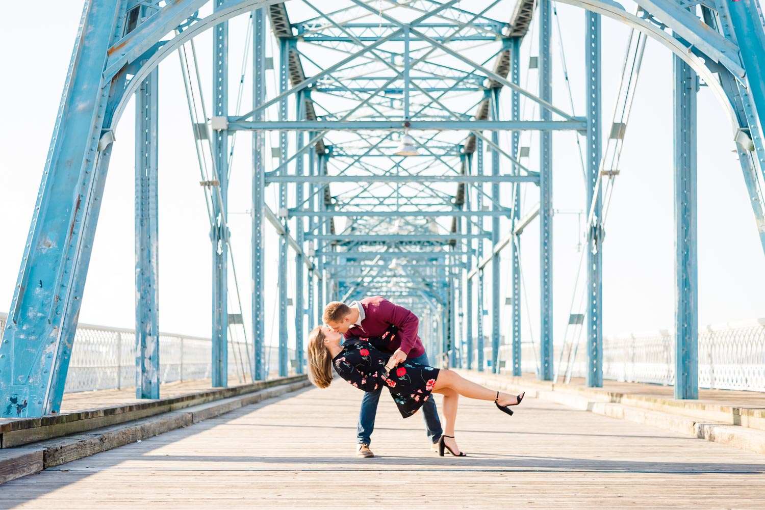 guy dipping his fiance for a kiss in the middle of the Walnut Street Bridge in Chattanooga TN