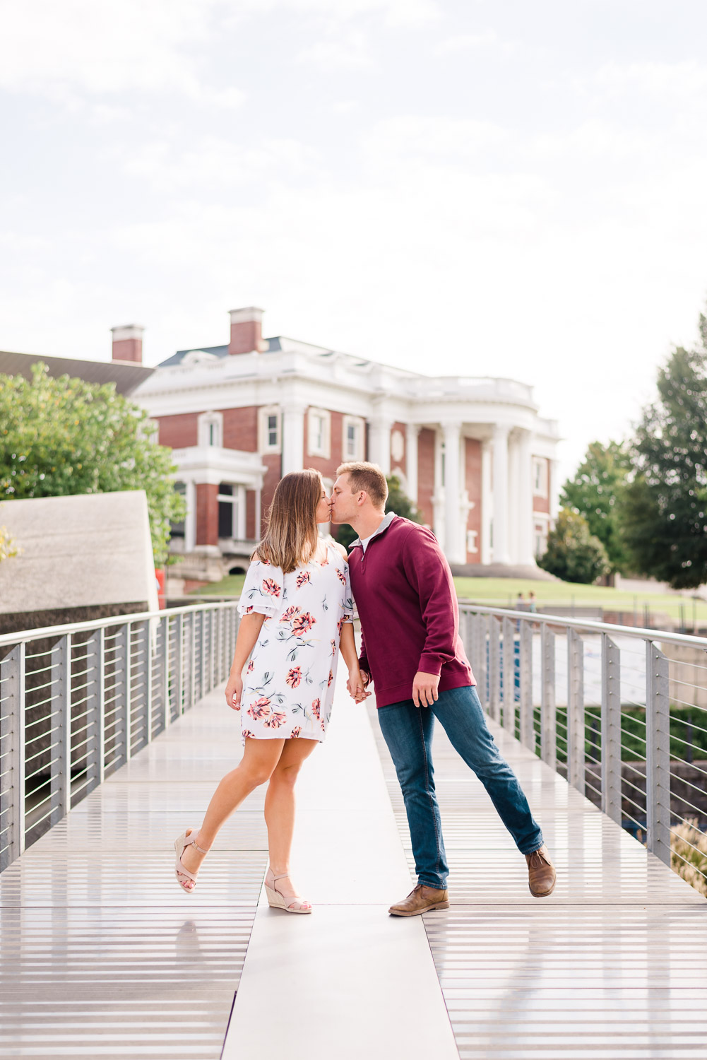 An engaged couple stopping for a kiss on the glass walking bridge to Hunter museum in Chattanooga TN