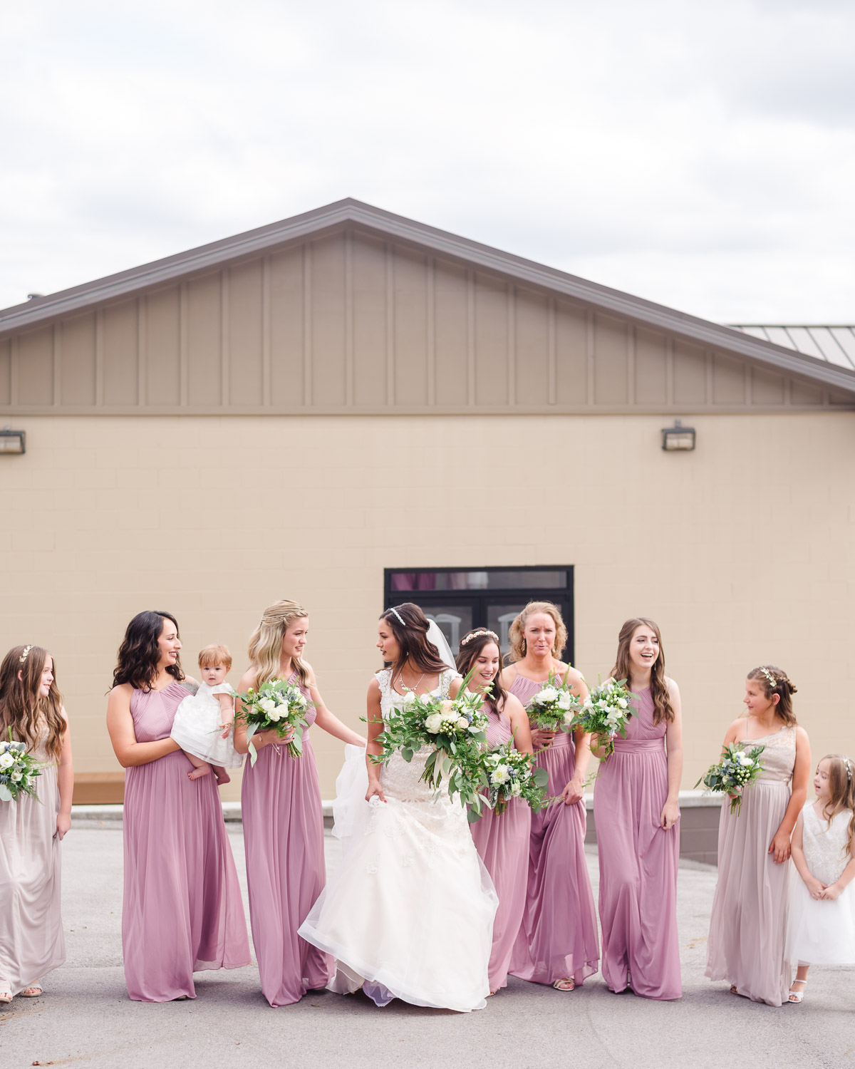 bride and her bridesmaids wearing a lavendar/mauve colored dresses walking outside lauging and talking in Knoxville