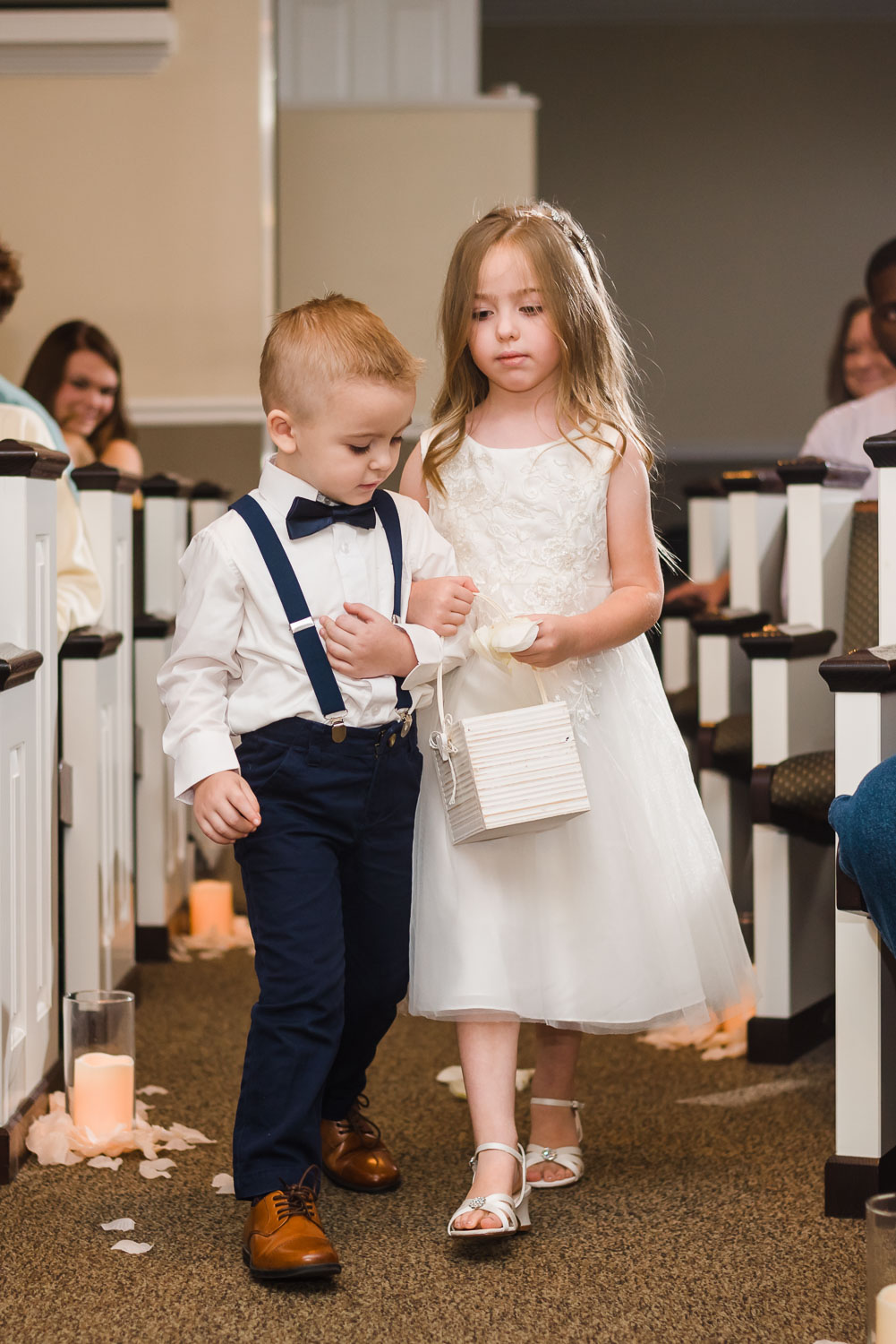 little ring bearer walking arm in arm with the flower girl into the church.