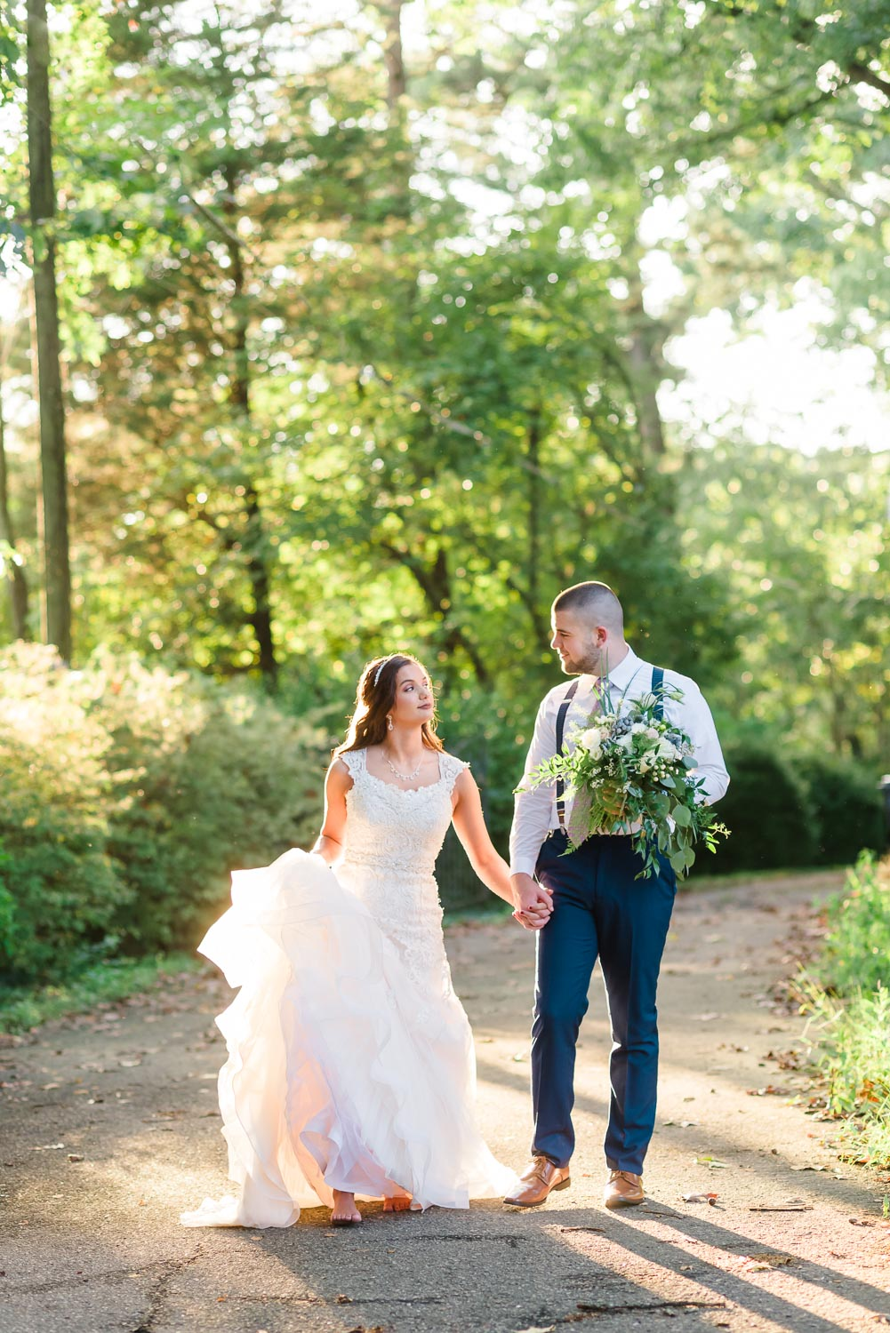 wedding couple walking down path in Knoxville at their september wedding before the leaves change