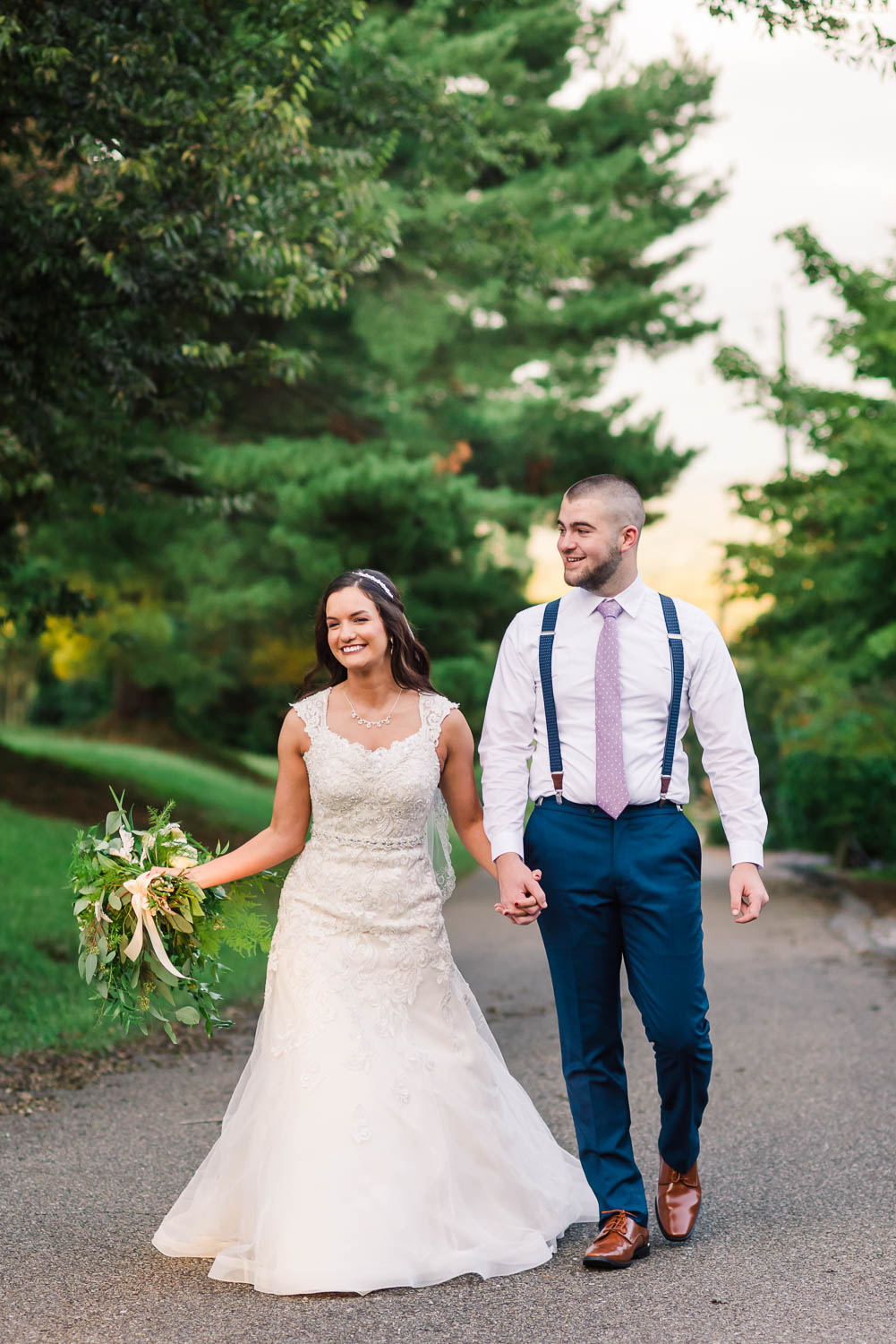 bride wearing white lace wide strap wedding dress and groom wearing white shirt and navy dress pants walking outside in Knoxville TN.