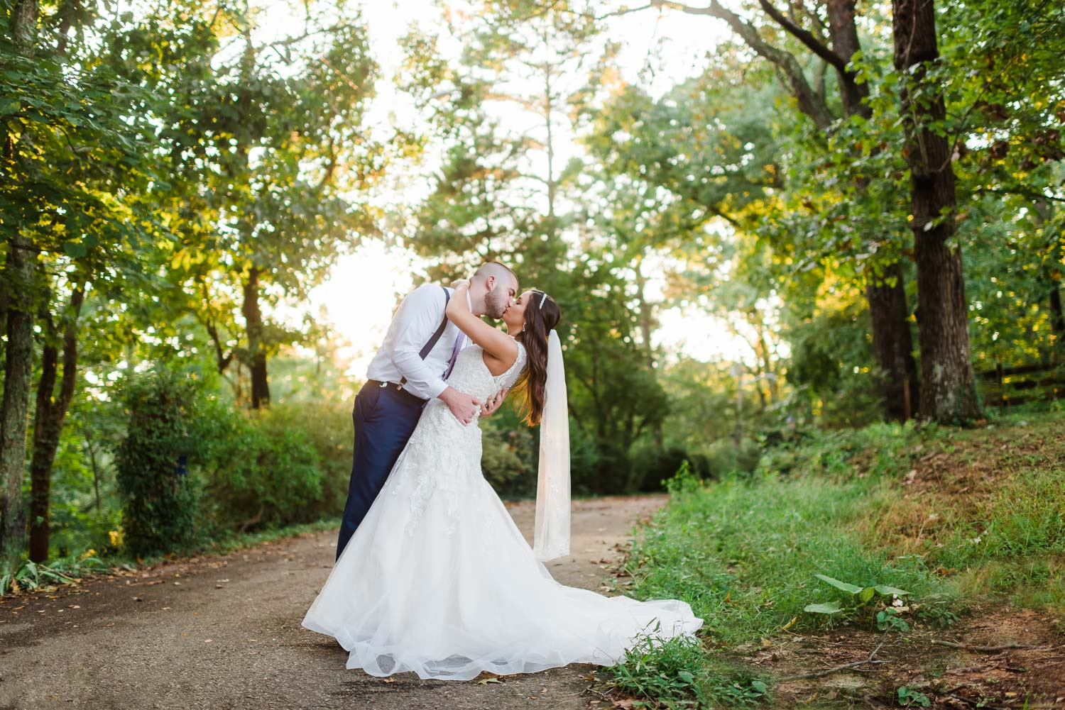 wedding couple outside at sunset in Knoxville TN with sunlight coming through the trees onto them.