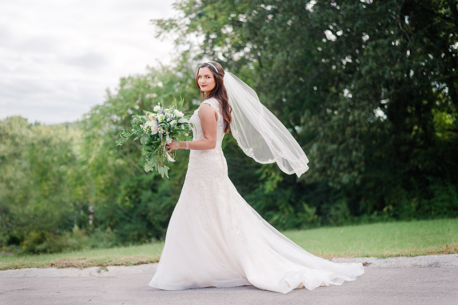 bride holding her bouquest outside with the wind blowing her veil in Knoxville before her wedding ceremony