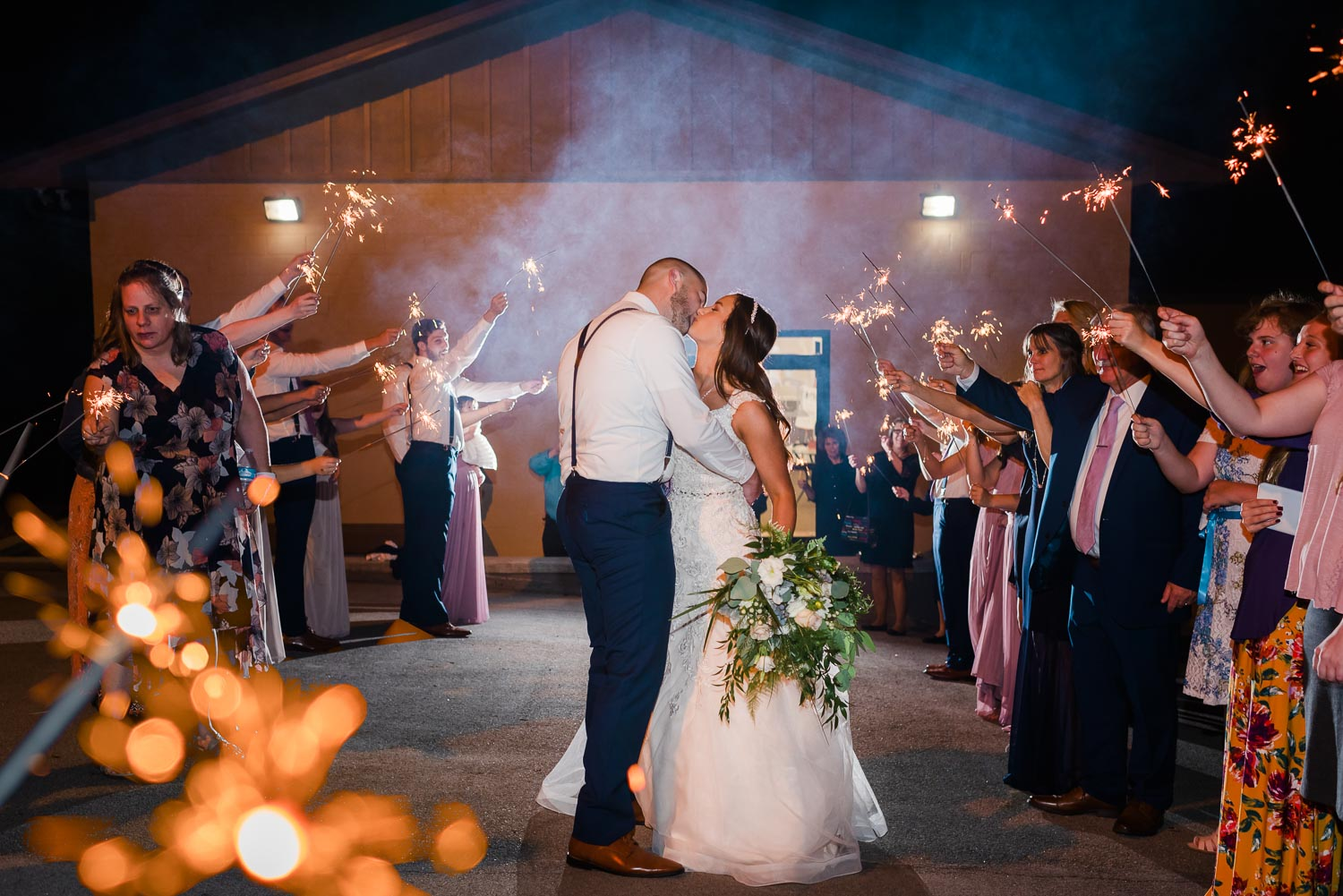 bride and groom stopping for a kiss during their sparkler exit from their wedding.