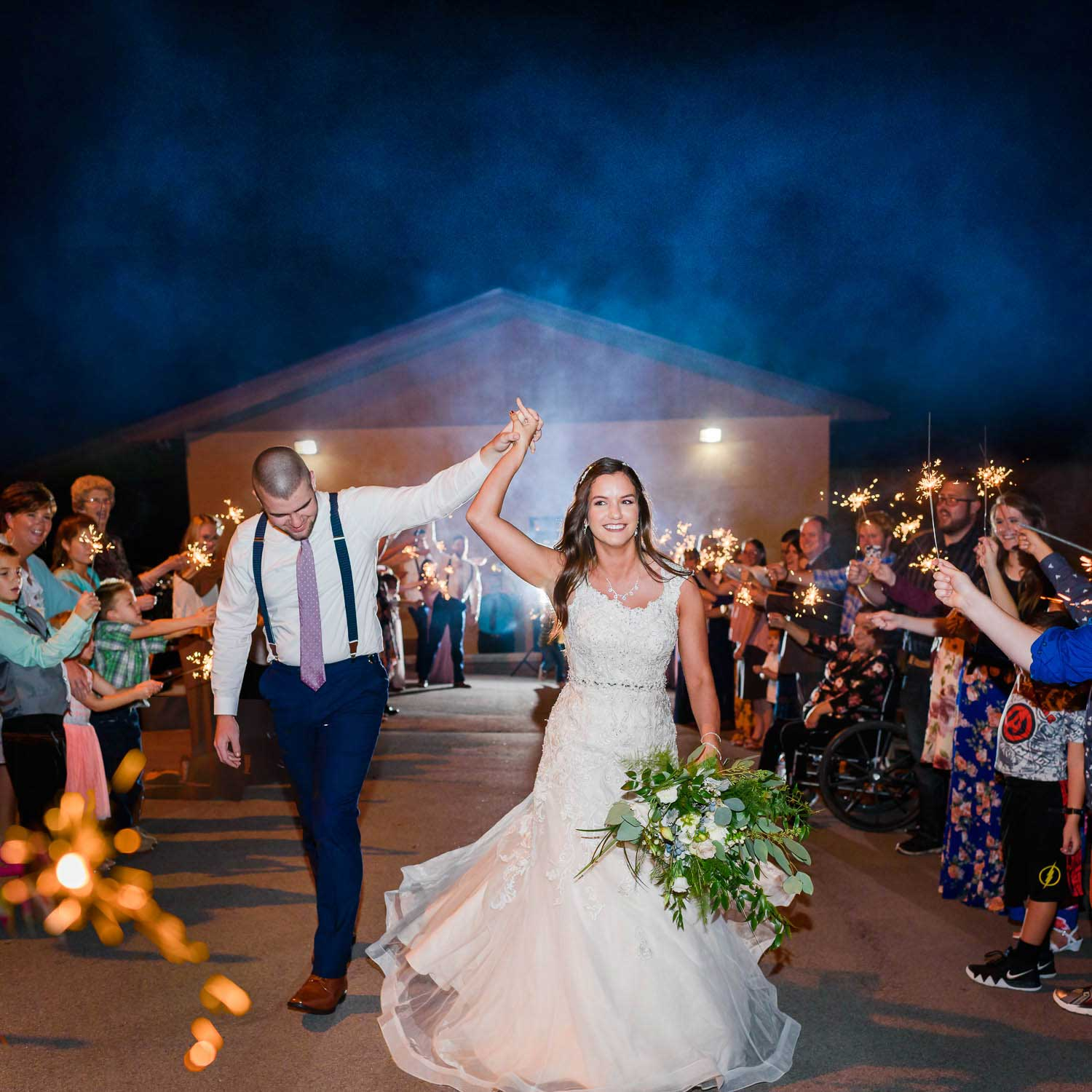 Bride and groom cheering as they leave with a nighttime wedding sparkler exit in Knoxville TN