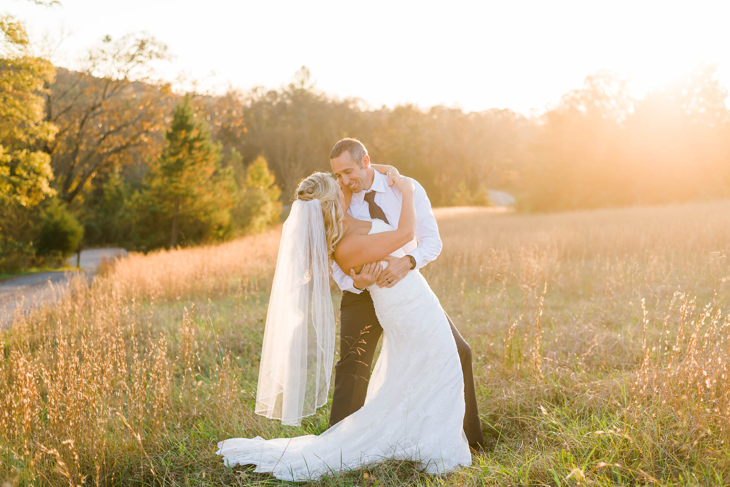 wedding couple out in tall hay field at sunset at the Barn at Drewia Hill in east Tennessee