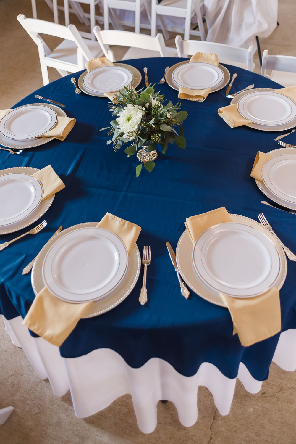 navy tablescape with white flowers and greenery