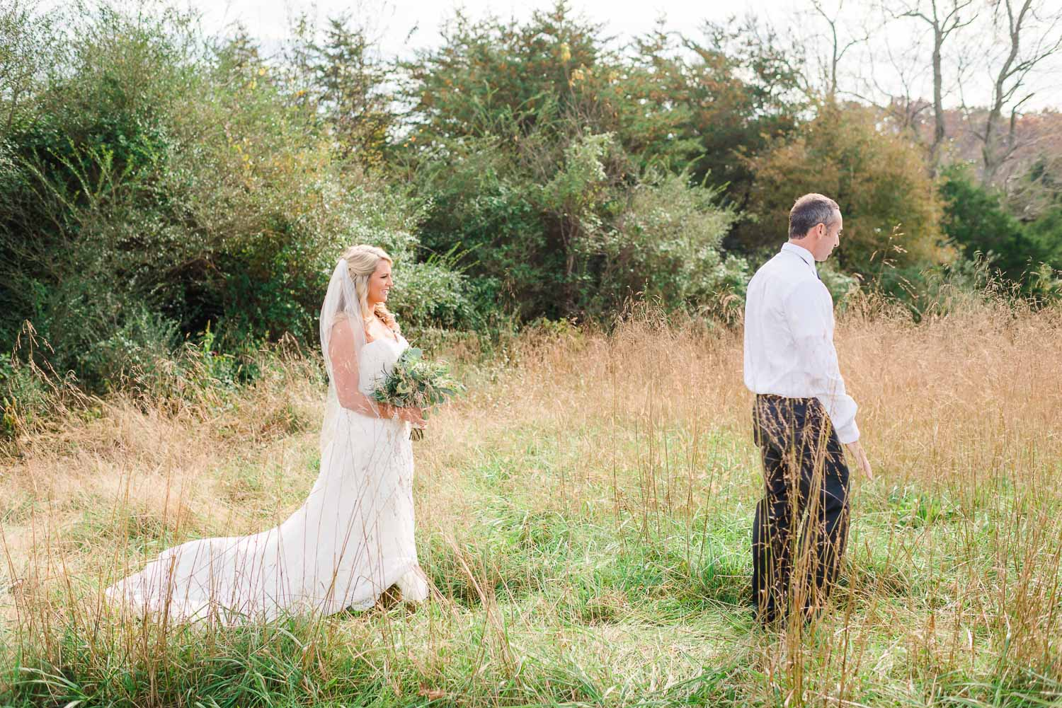 bride walking up to the groom outside in tall grass at The Barn at drewia hill