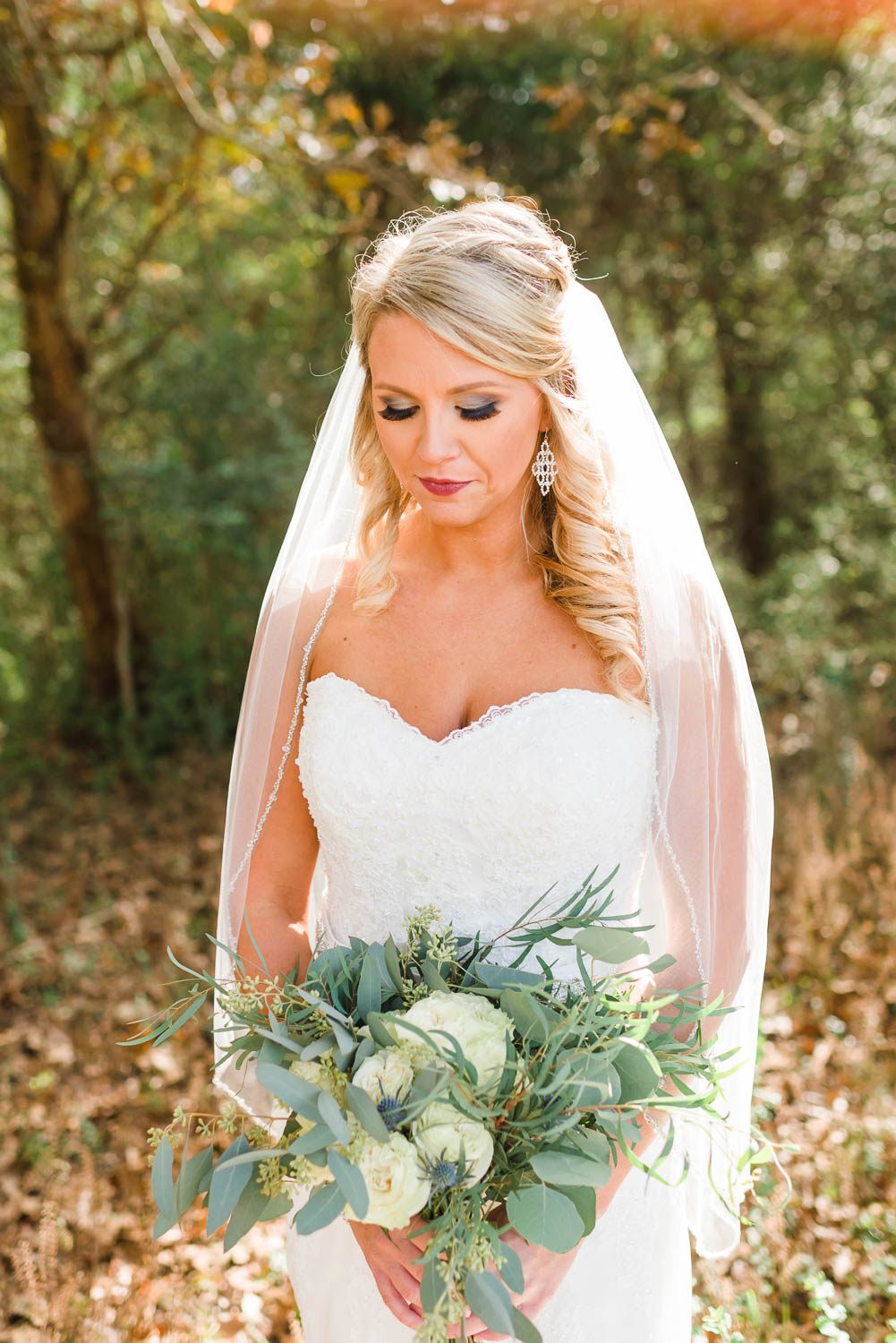 lovely bride outside with greenery bouquet and veil